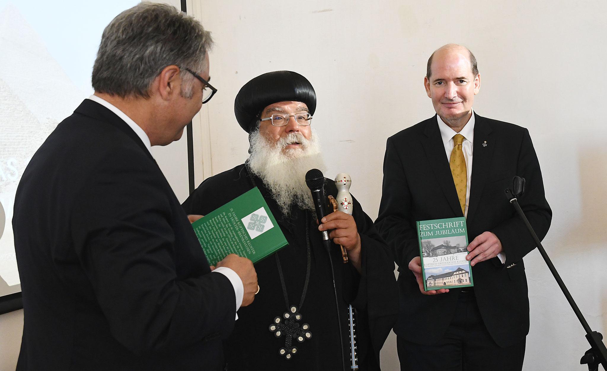 S.E. Bischof Anba Damian bedankt sich bei Martin Lohmann und Dr. h.c. Michael Hesemann mit einer Festschrift zum Jübiläum. Foto: Maria Hopp