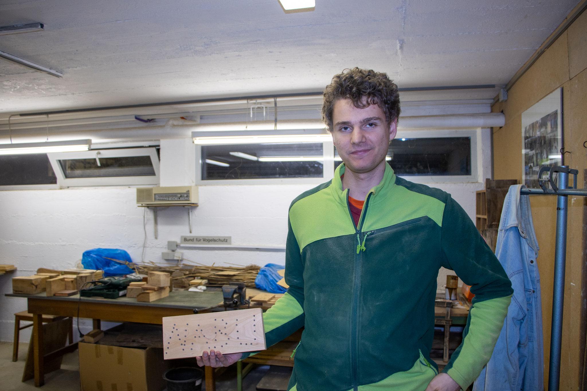 Marwin präsentiert den fertigen Holzblock mit dem NABU-Schriftzug (Foto: B. Budig)