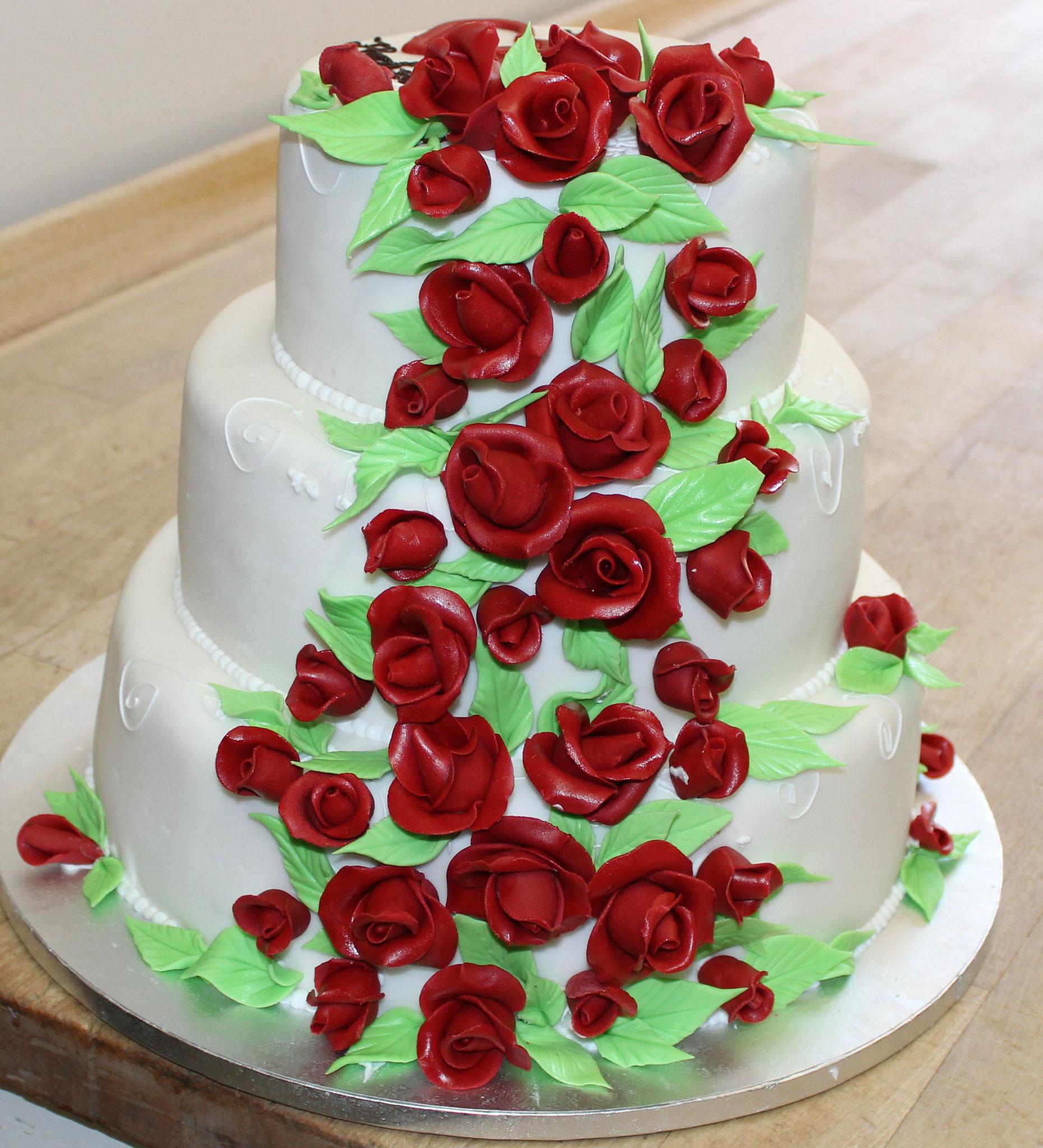Hochzeitstorte mit vielen roten Rosen