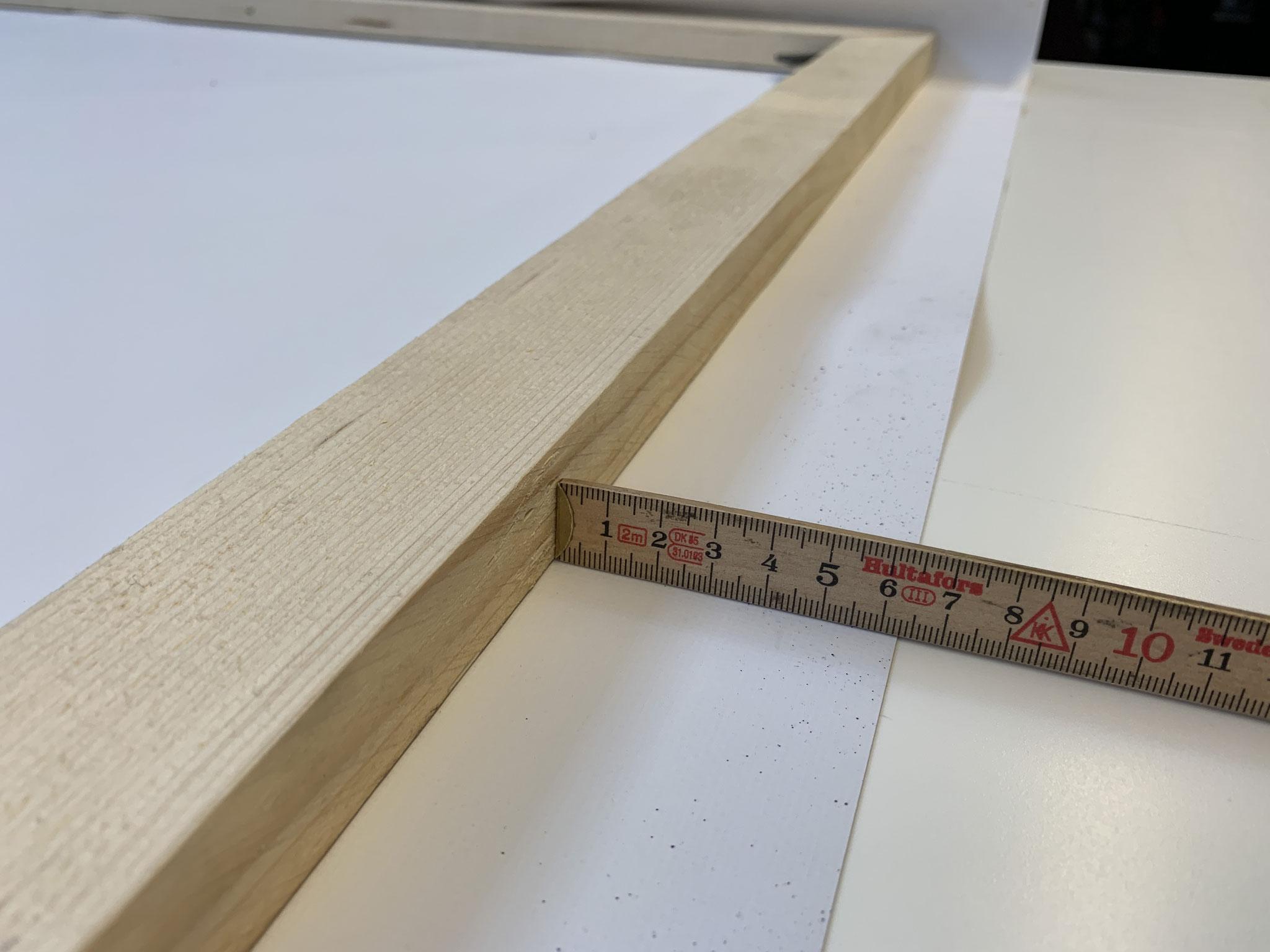 Das Bild mit der Rückseite nach oben auf einen ebenen und weichen Untergrund legen. Den Rahmen darauf legen und genau auf dem Banner zentrieren.