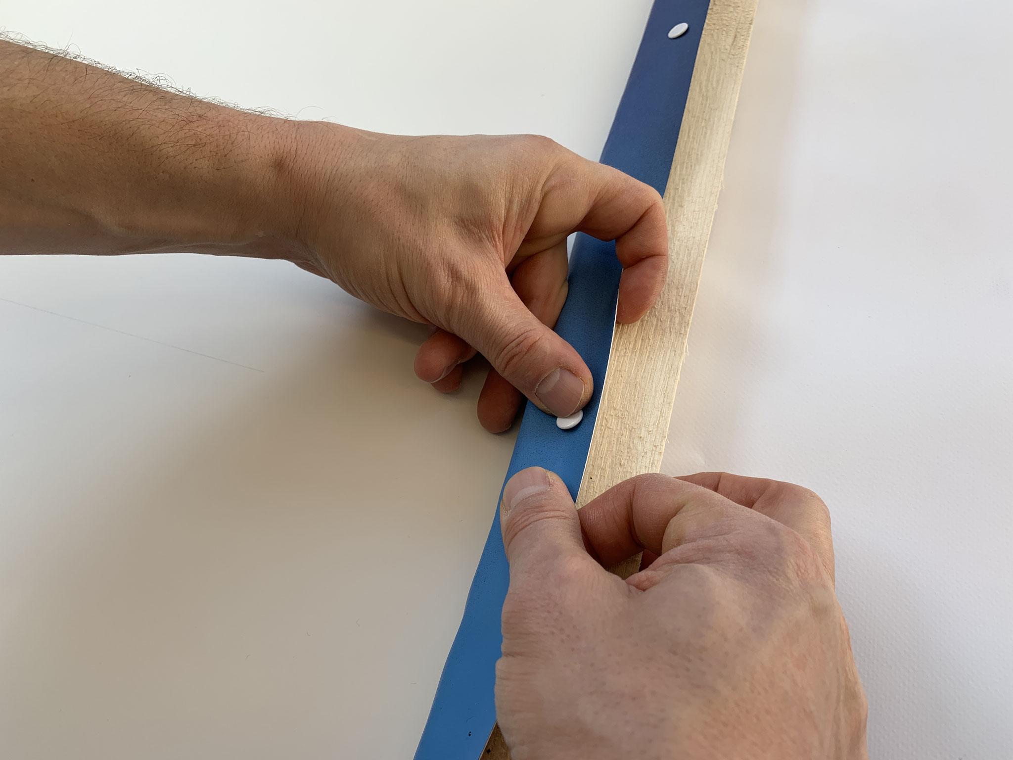 Den Banner jeweils in der Mitte nach Oben klappen und mit den Reisnägeln befestigen. Tipp: Je Seite in der Mitte anfangen und nach aussen arbeiten. Am Schluss die Ecken einlegen.