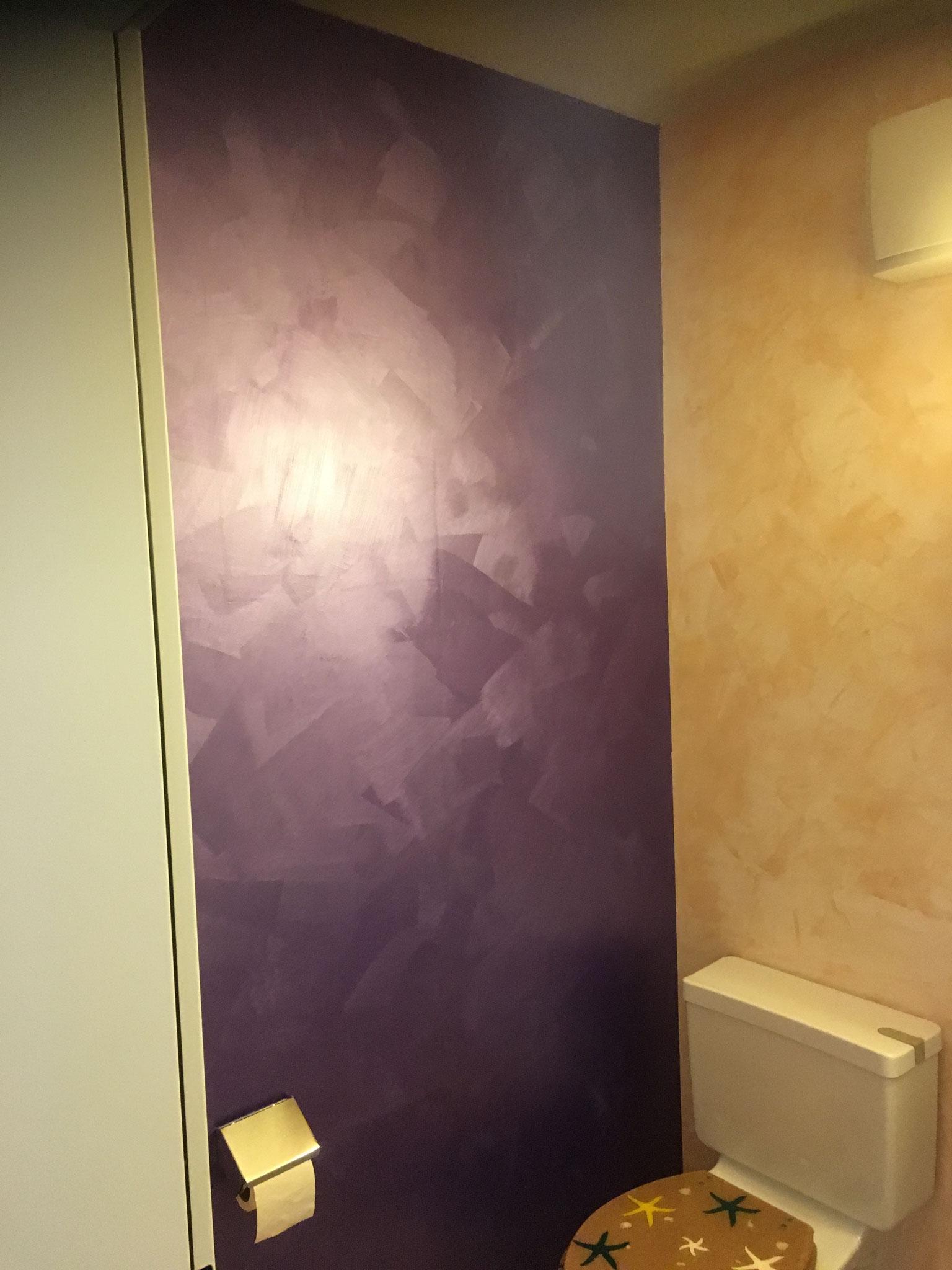 """Die anliegende Wand ist mit dem System """"Sabulador-Soft"""", im Farbton """"Violett"""" gestaltet. Die leicht sandige Oberfläche und der Glanz gibt der Wand einen speziellen Touch."""