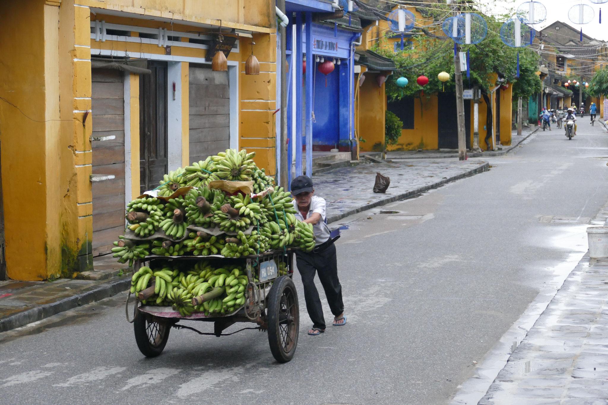Frühmorgens schieb ein Händler siene Waren auf den Markt