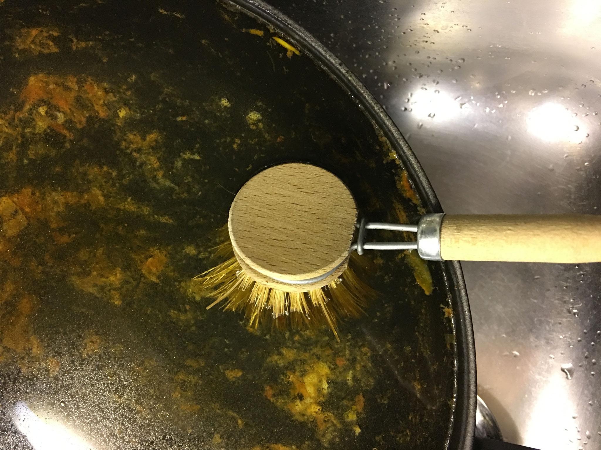 Dann mit einer Spülbürste die Speisereste komplett lösen.