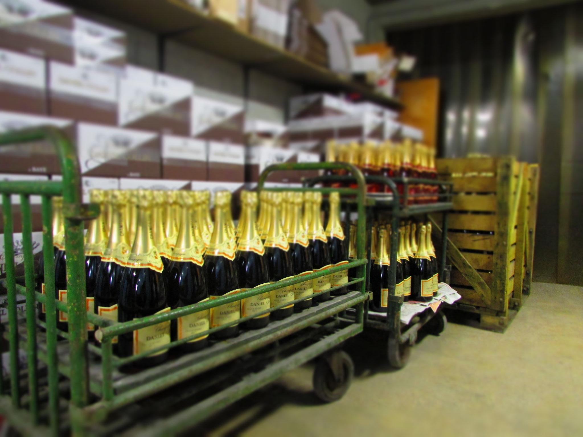 En cave, les bouteilles habillées attendent d'être mises en carton