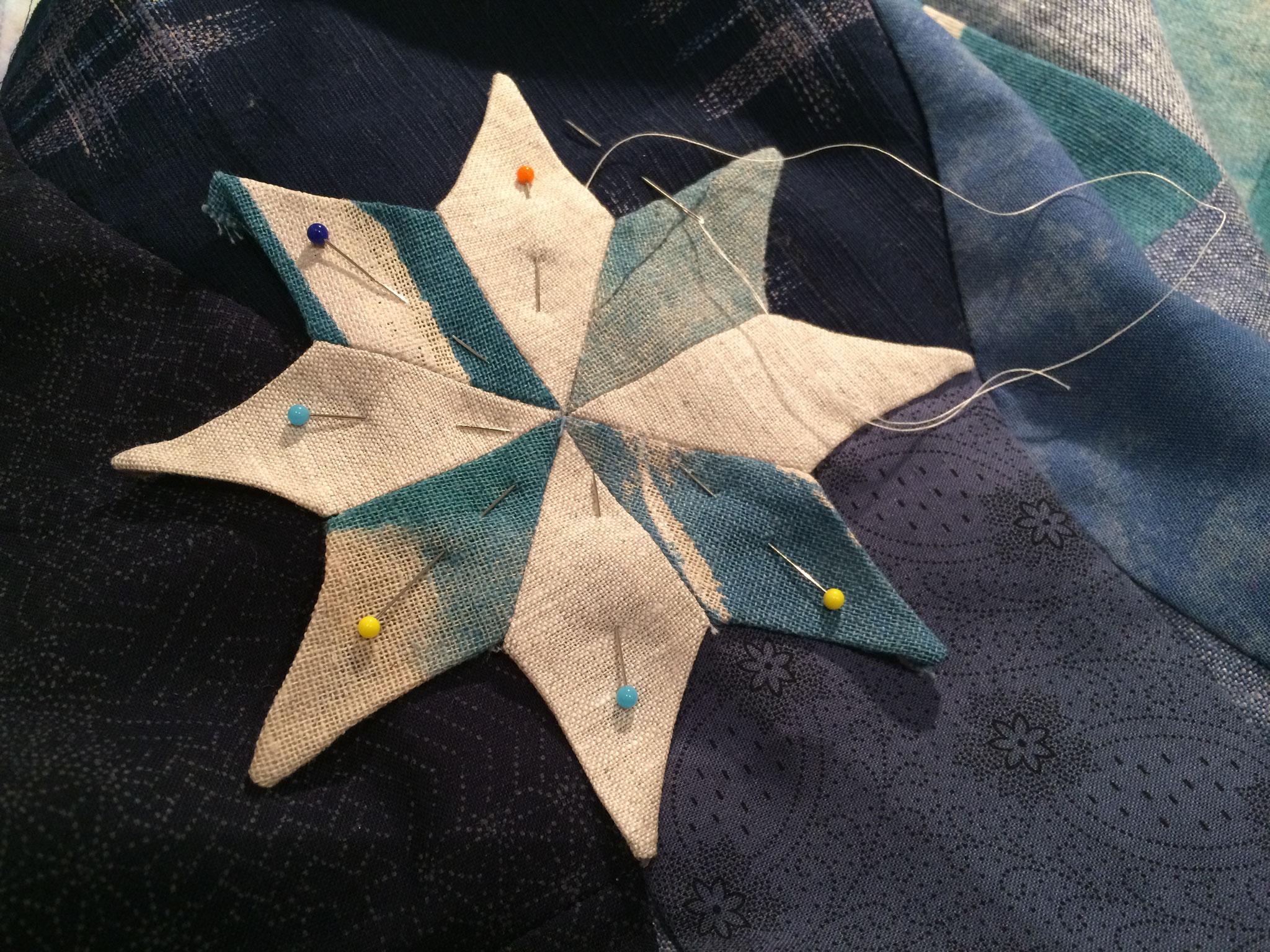 Appliqué de l'étoile à la main. Tissu imposé.