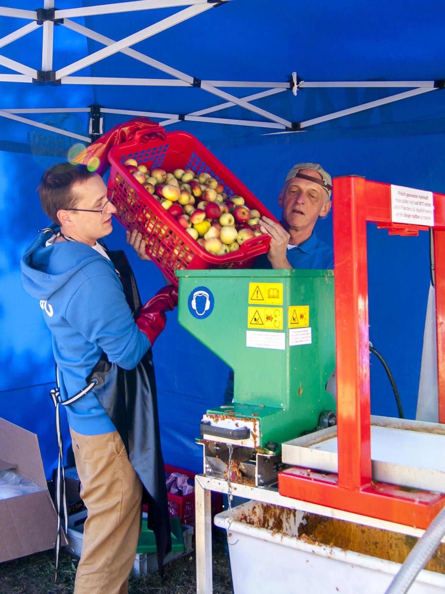 Nick Büscher und Günter Groß an der Apfelpresse. - Foto: Kathy Büscher