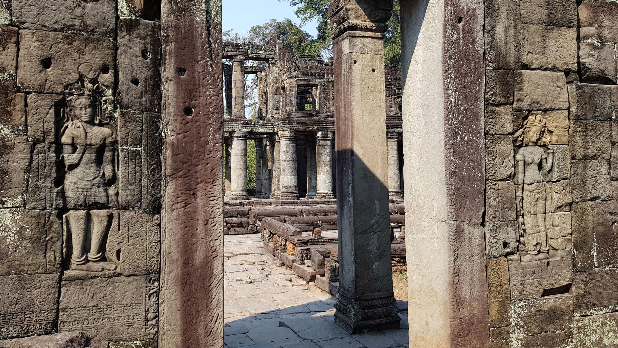 Entrée nord, côté intérieur, de la salle de danse du Preah Khan d'Angkor, flanquée de deux personnages féminins à chignon à triple boucle.