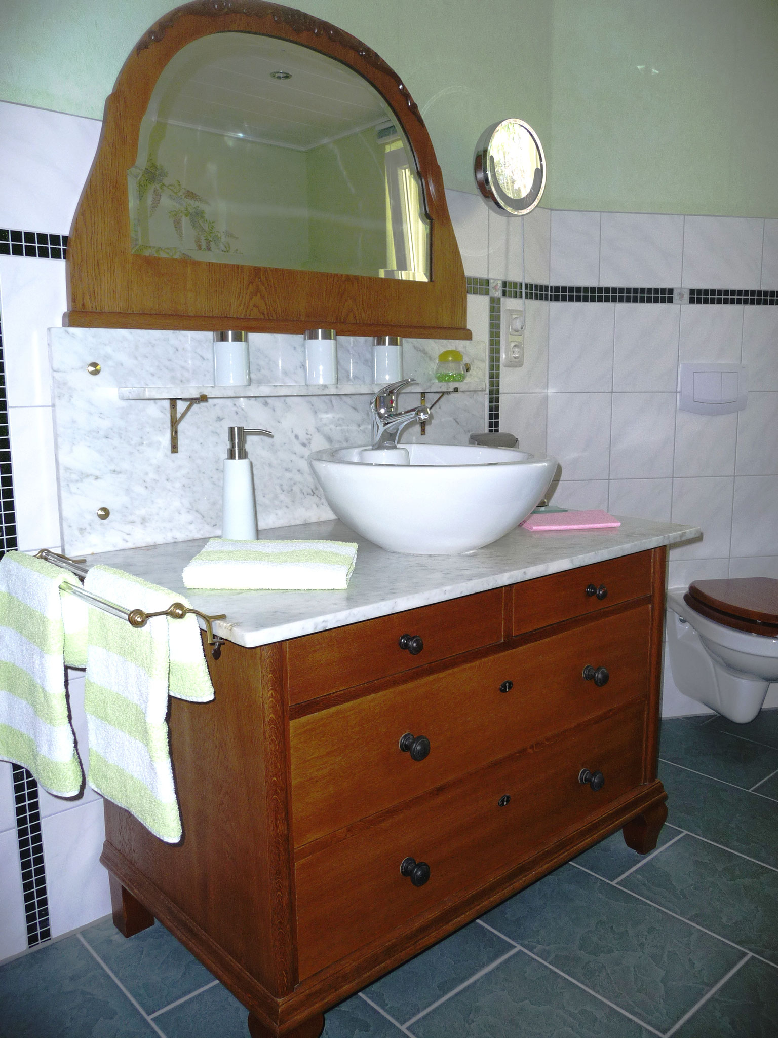 Der Waschtisch aus der Zeit um 1890 mit Marmorplatte und aufgesetztem Waschbecken ist kunstvoll aufgearbeitet und modern ausgestattet.