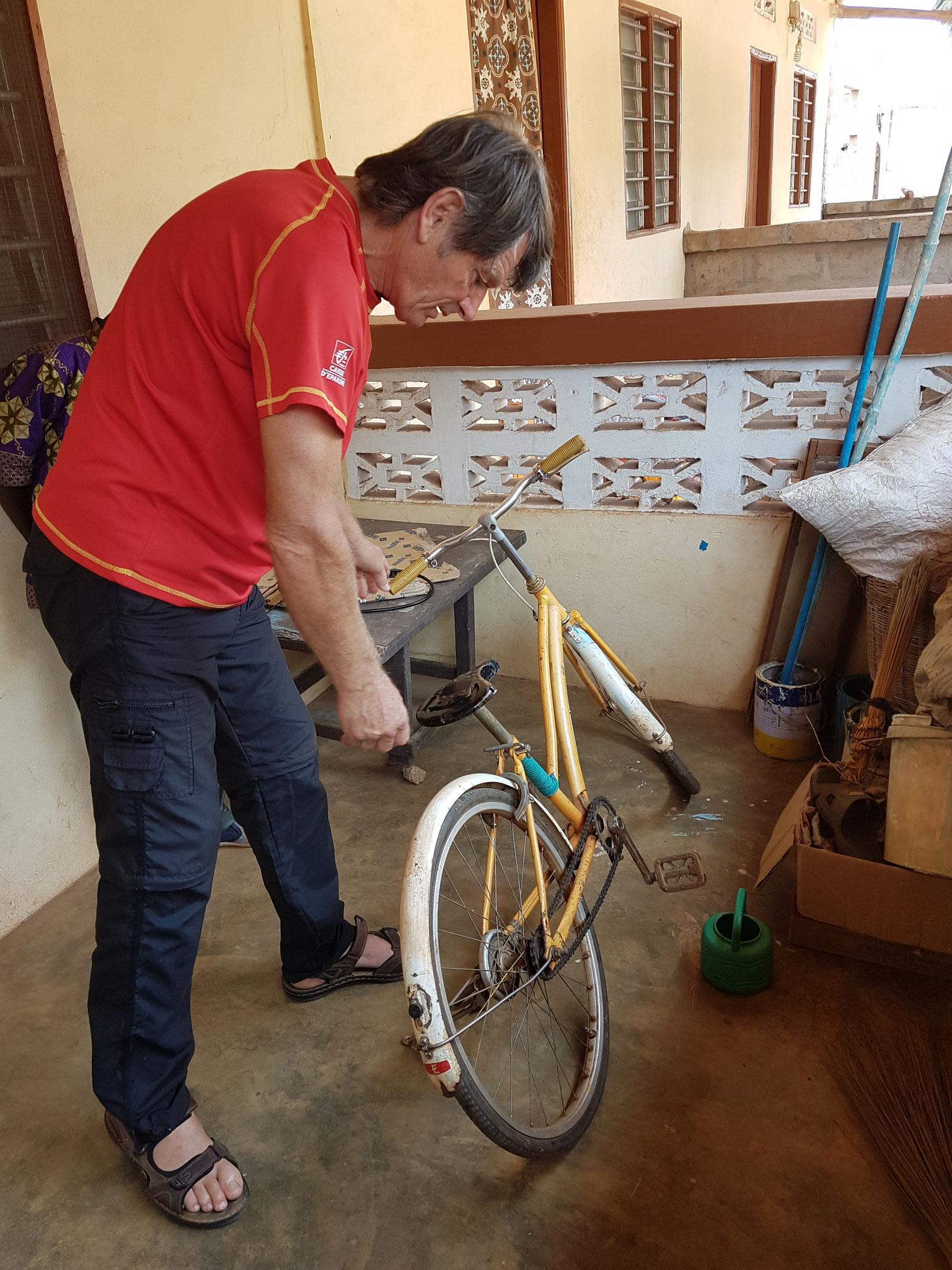 Jean Paul réparant une bicyclette