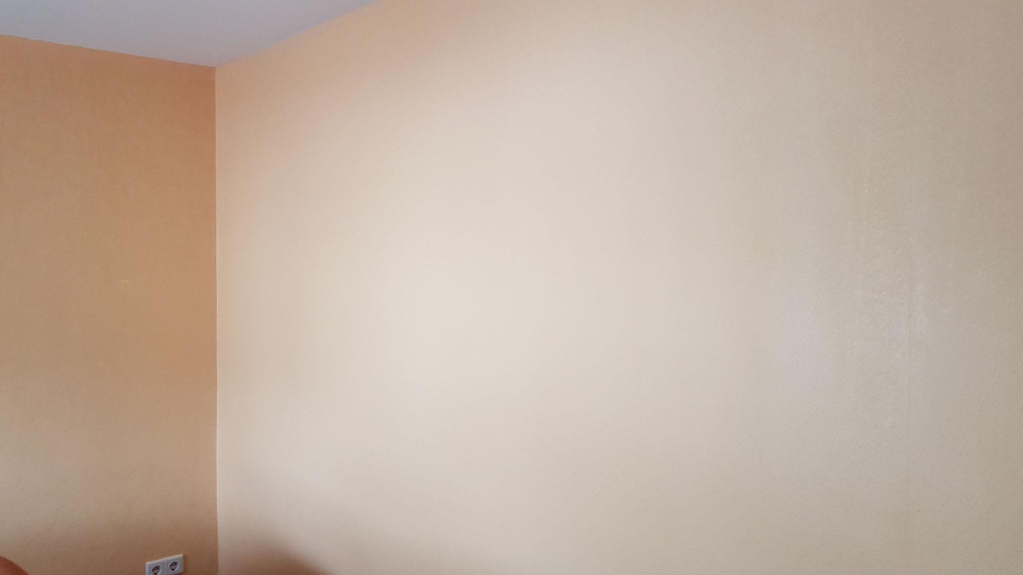 Fertig tapezierte und gestrichene Wohnzimmerwand.