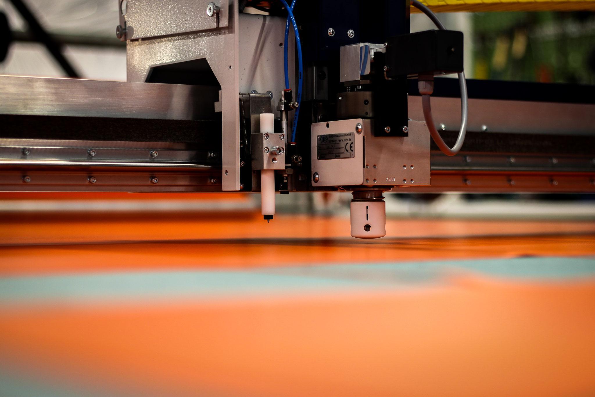 Zu Beginn werden Planenmaterial und Baumwollstoff zugeschnitten. Die Rolle mit dem Rohmaterial wickelt sich hierbei automatisch ab, während ein Messer die zuvor programmierten Wege abläuft