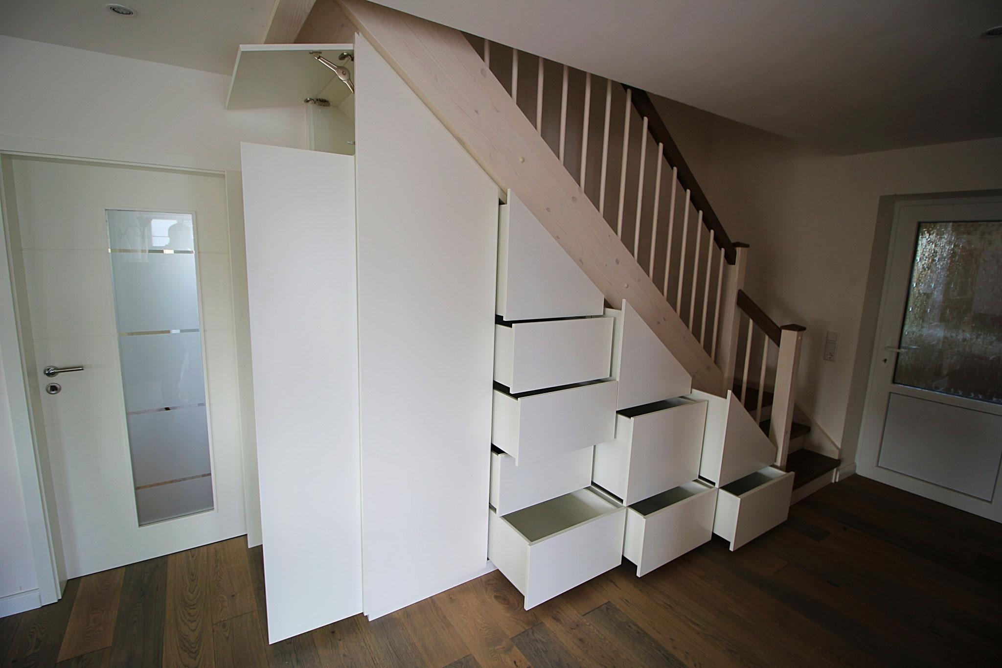 unter dem langen Lauf der Treppe drei nebeneinander stehende Schrankelemente