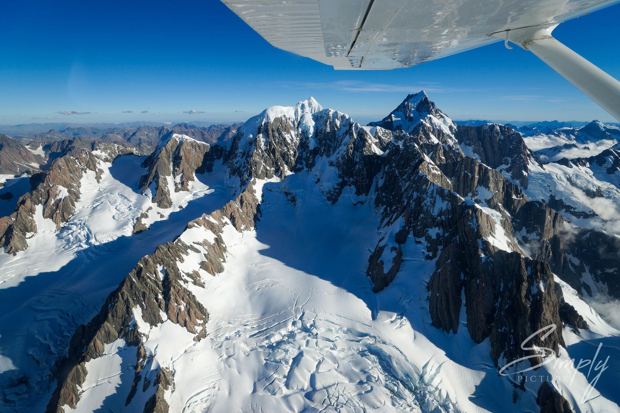 Flug über die südlichen Alpen, weisser Flügel des Flugzeugs und Blick auf den Mount Cock mit Schnee und Eis