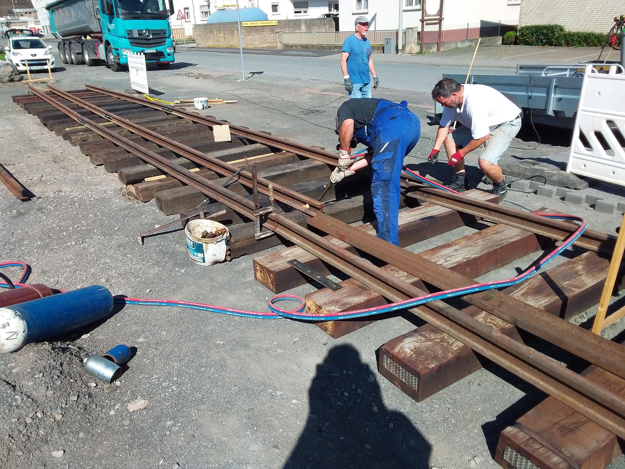Alexander Kirchner mit Jürgen Reis verschrauben die letzten Schienenstücke mit  Laschen