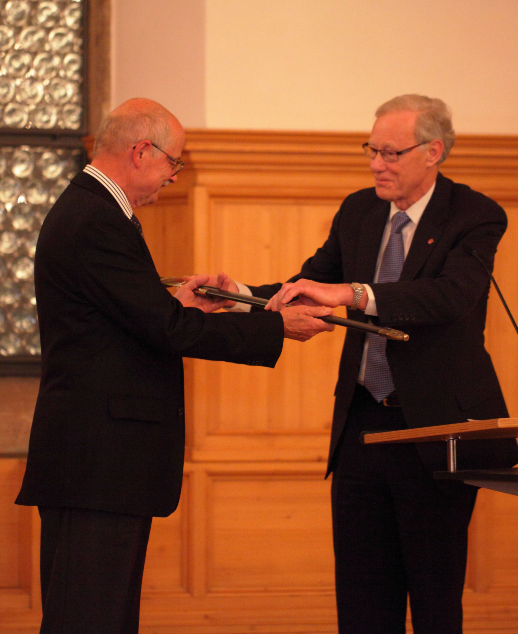Prof. Johan Meijer (right) is giving the Knights' sword to Prof. Manfred Geiger (left) at LANE 2010