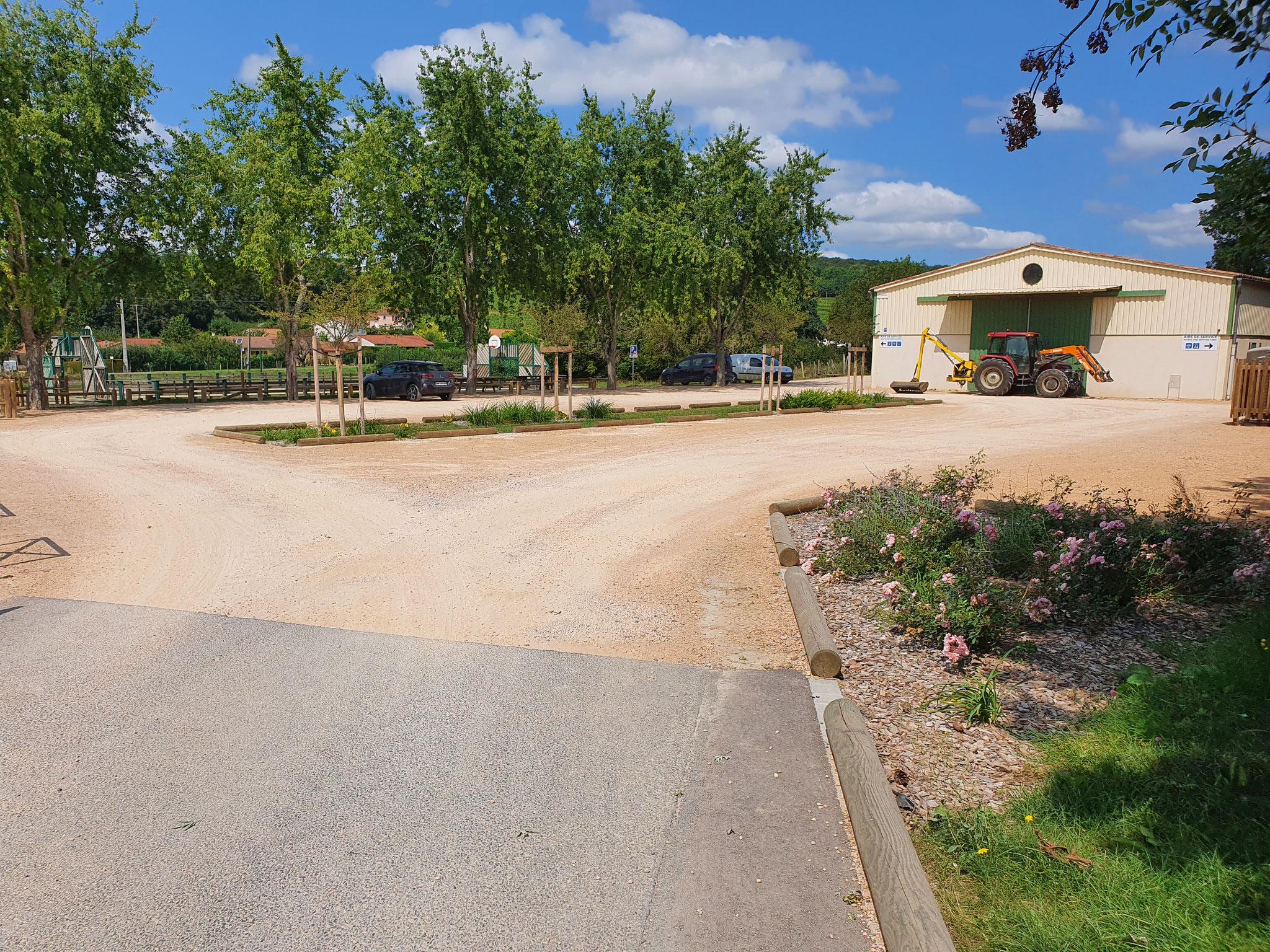 Parking fonctionnel aux abords de l'école avec noue central d'infiltration