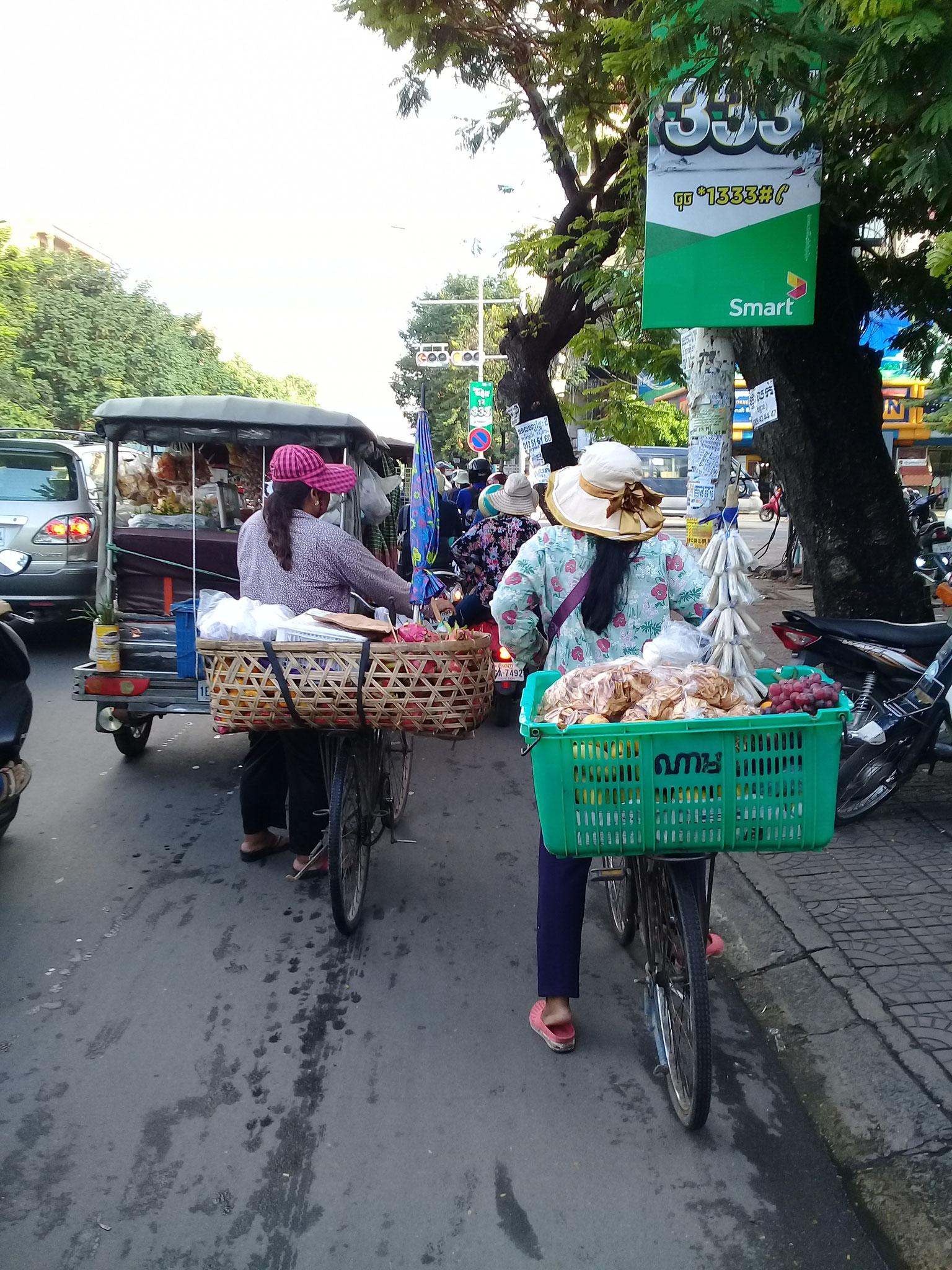 diese zwei Damen fahren ihre Verkaufsstände durch die Gegend, dahinter: ein gut beladenes Tuk Tuk
