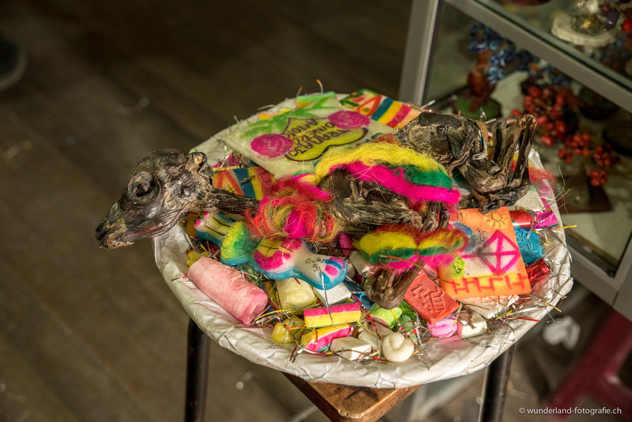 Schale für traditionelle Rituale mit Zuckerbonbons, Figürchen, Kräutern und einem Lamafötus