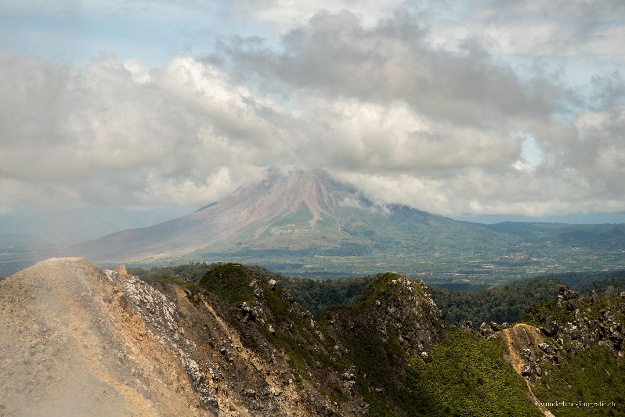In der Ferne sieht man den regelmässig ausbrechenden Vulkan Sinabung