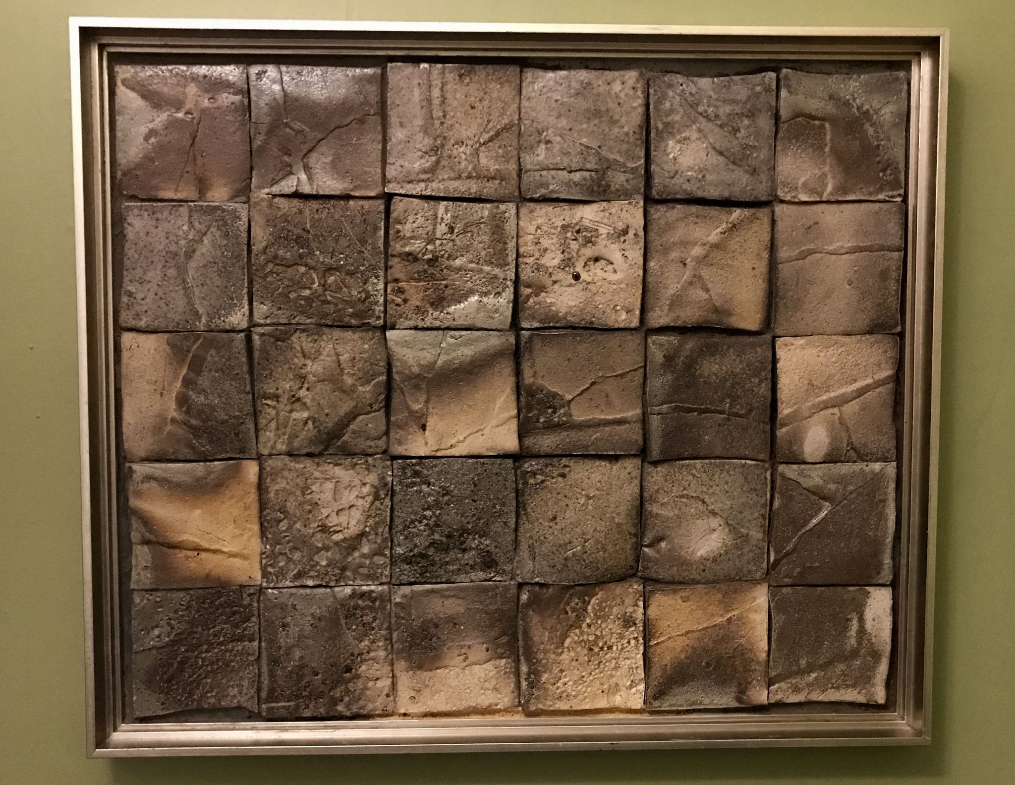 """Variant, 33.25"""" x 39.25"""" x 2.5"""". Wood fired tile wall panel framed w/silver wood."""