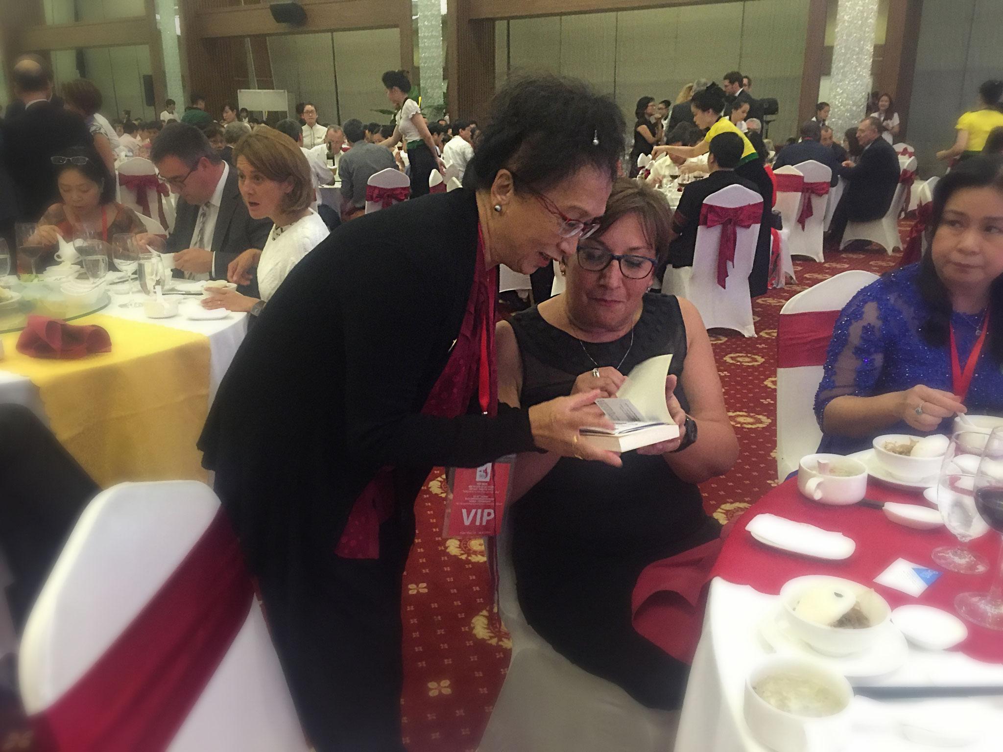Mme Pinville, Secrétaire d'État auprès du ministre de l'Économie et des Finances,  est ravie du cadeau offert par Anna  : le livre de Mohed Altrad