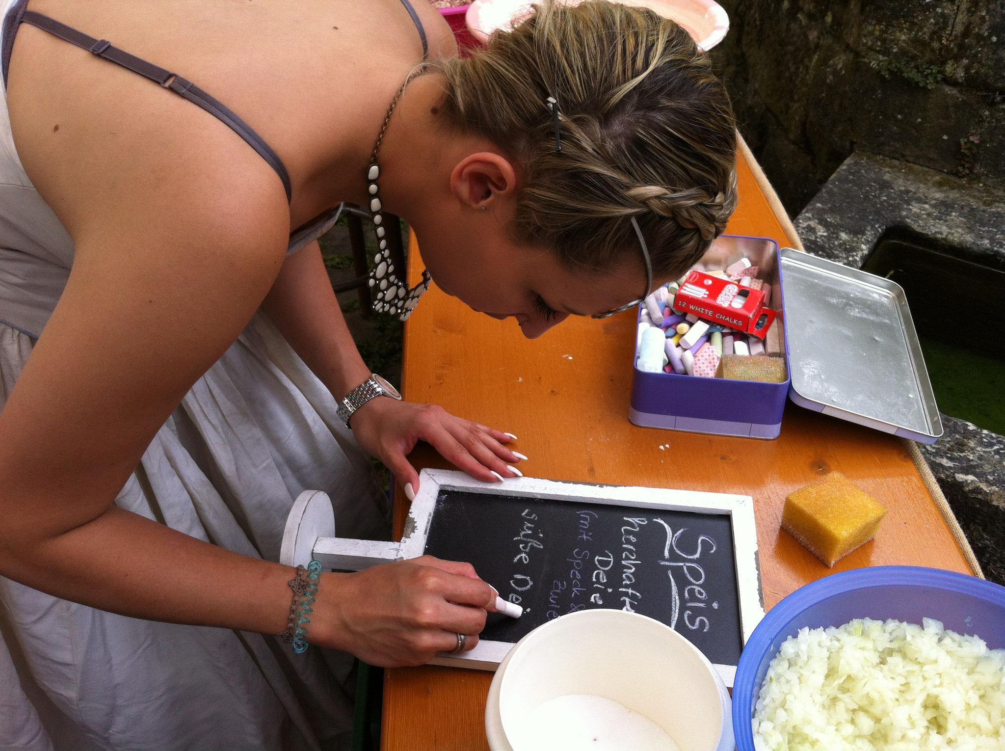 Nathalie schreibt die Angebotsschilder