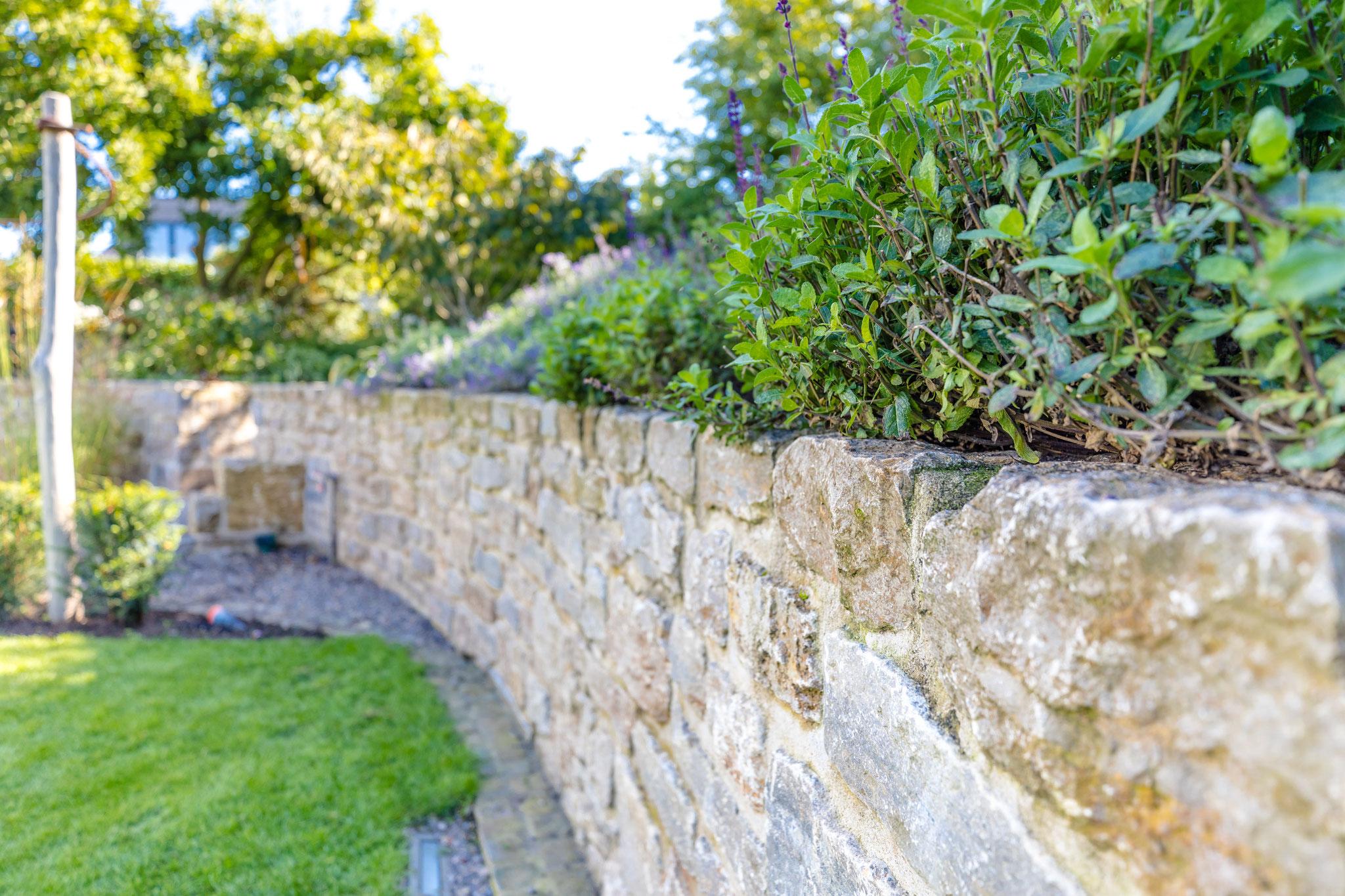 ...als Natursteinmauerwerk aus massiven Bruchsteinen im Garten