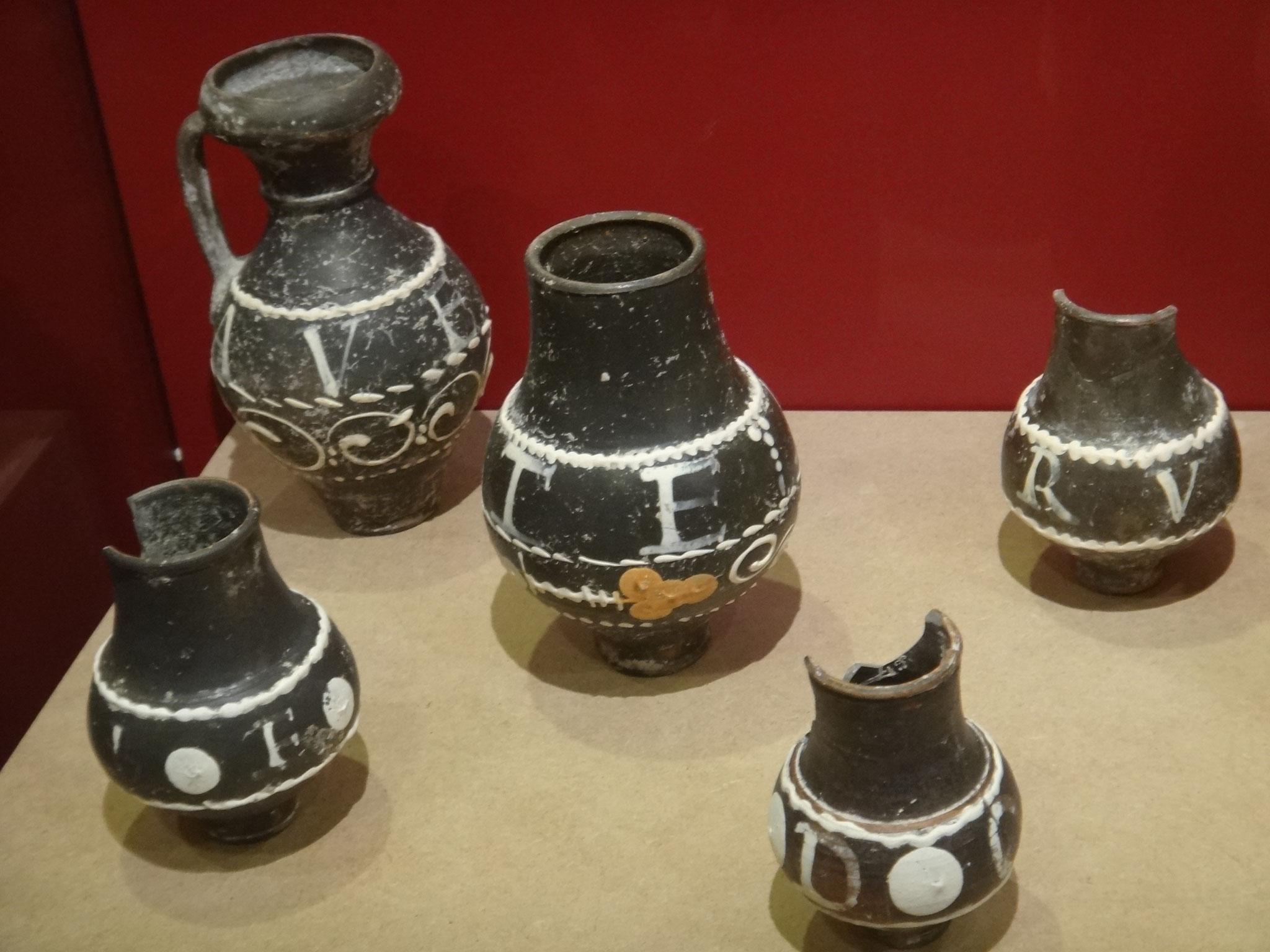Gobelets en céramique métallescente dont les surfaces noires sont ornées de décors en barbotine blanche avec des devises latines
