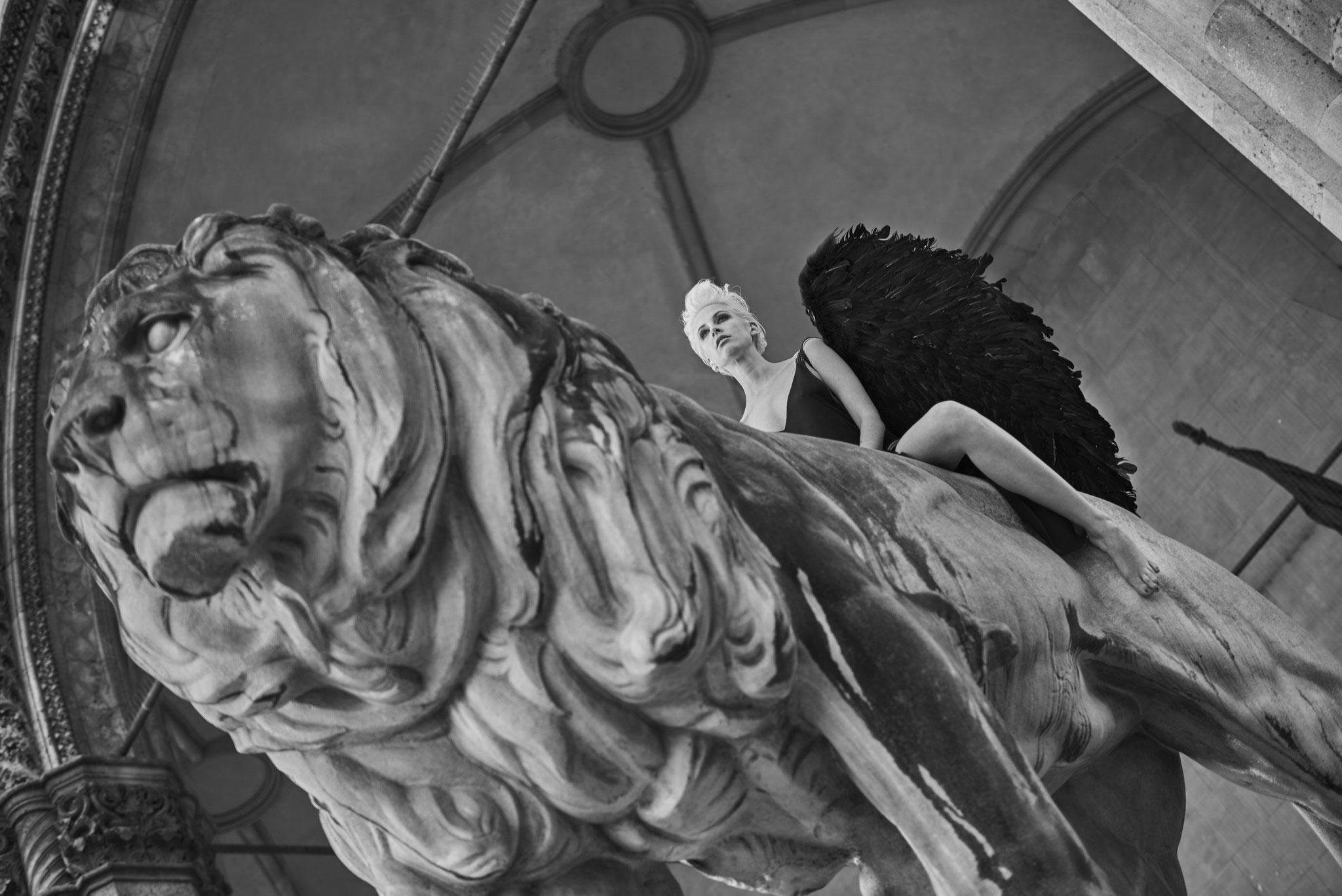 schwarz-weiß Porträt einer Frau, die auf einem Steinlöwen sitzt aus der Serie Women in Town