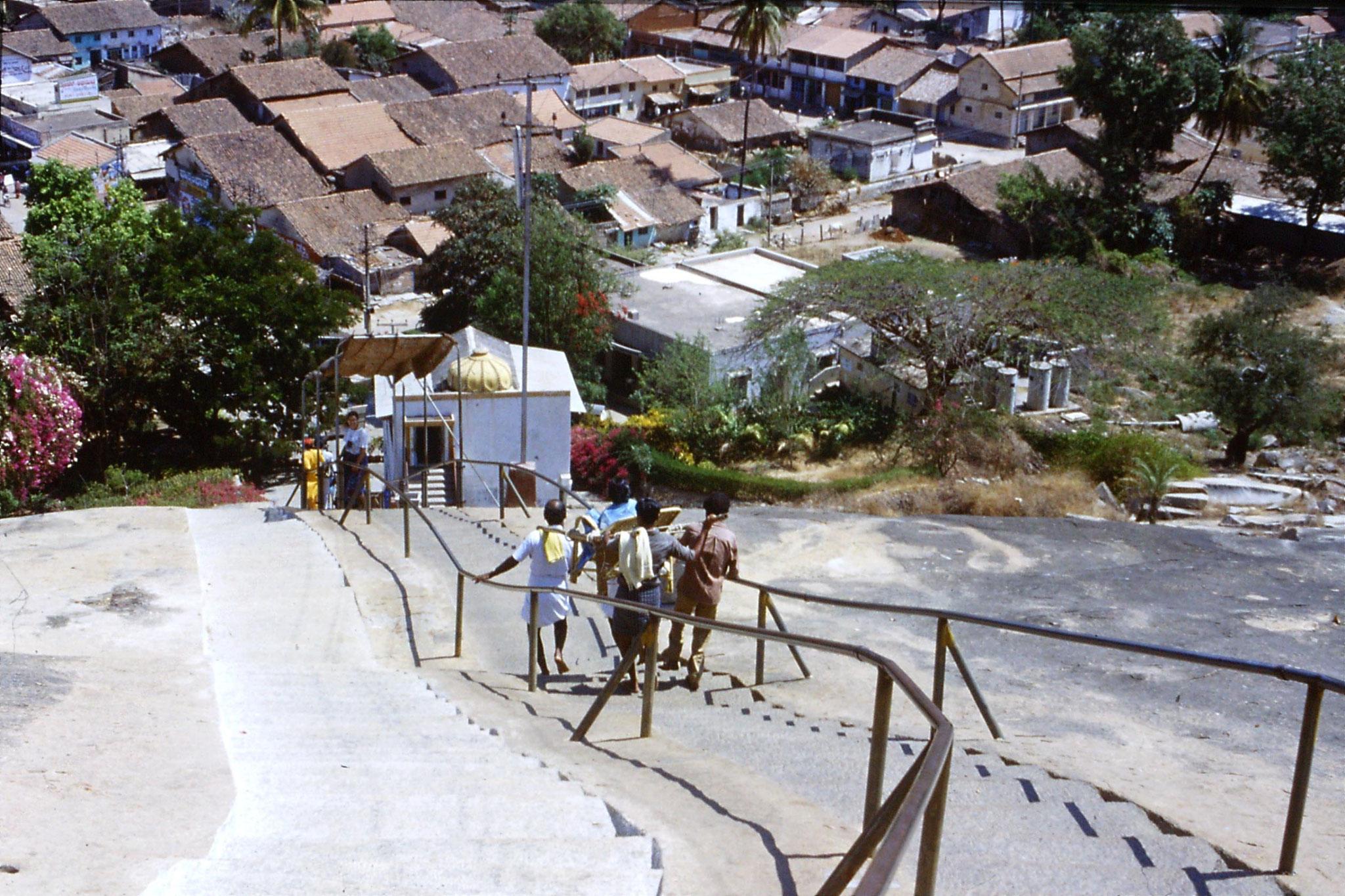 108/13: 13/3/1990 Sravanabelagola - woman carried on dholi, E behind