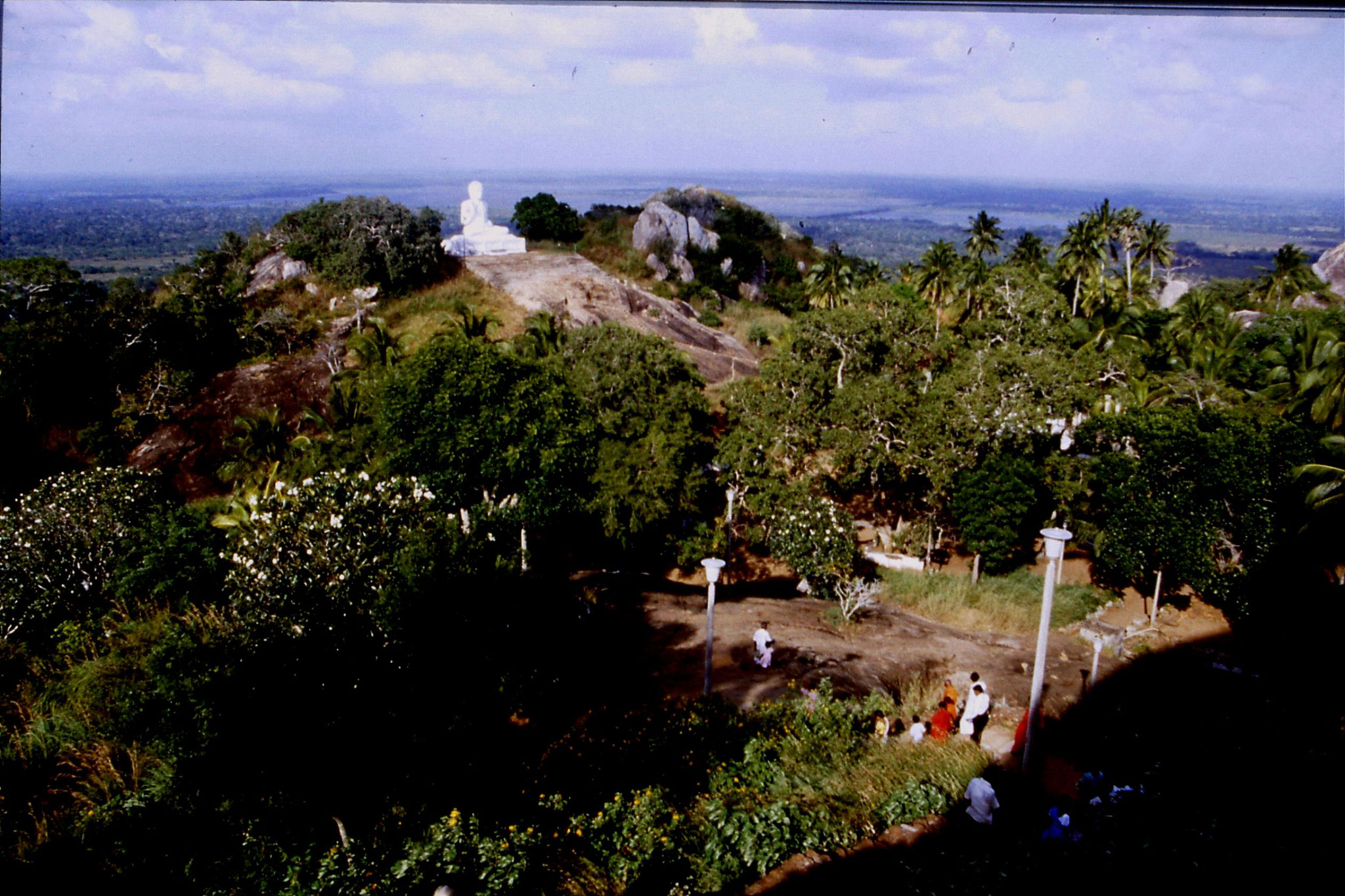 103/4: 8/2/1990 Buddha statue and monks with water behind at Mihintale