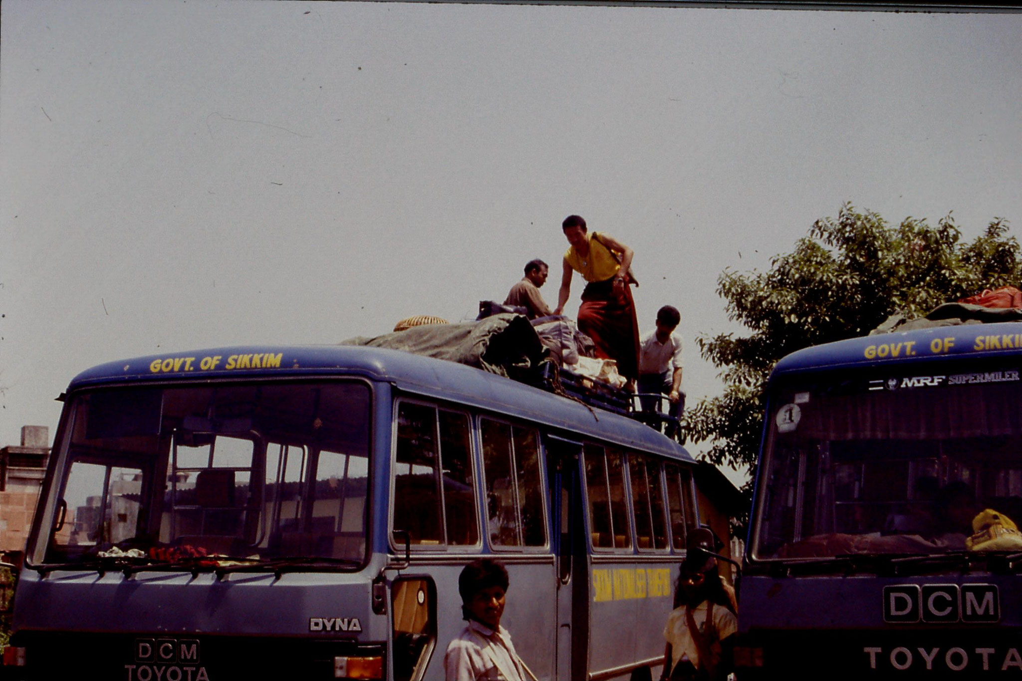 115/0: 21/4/1990 Siliguri (Assam) - Sikkim State Bus Depot - monk loading luggage