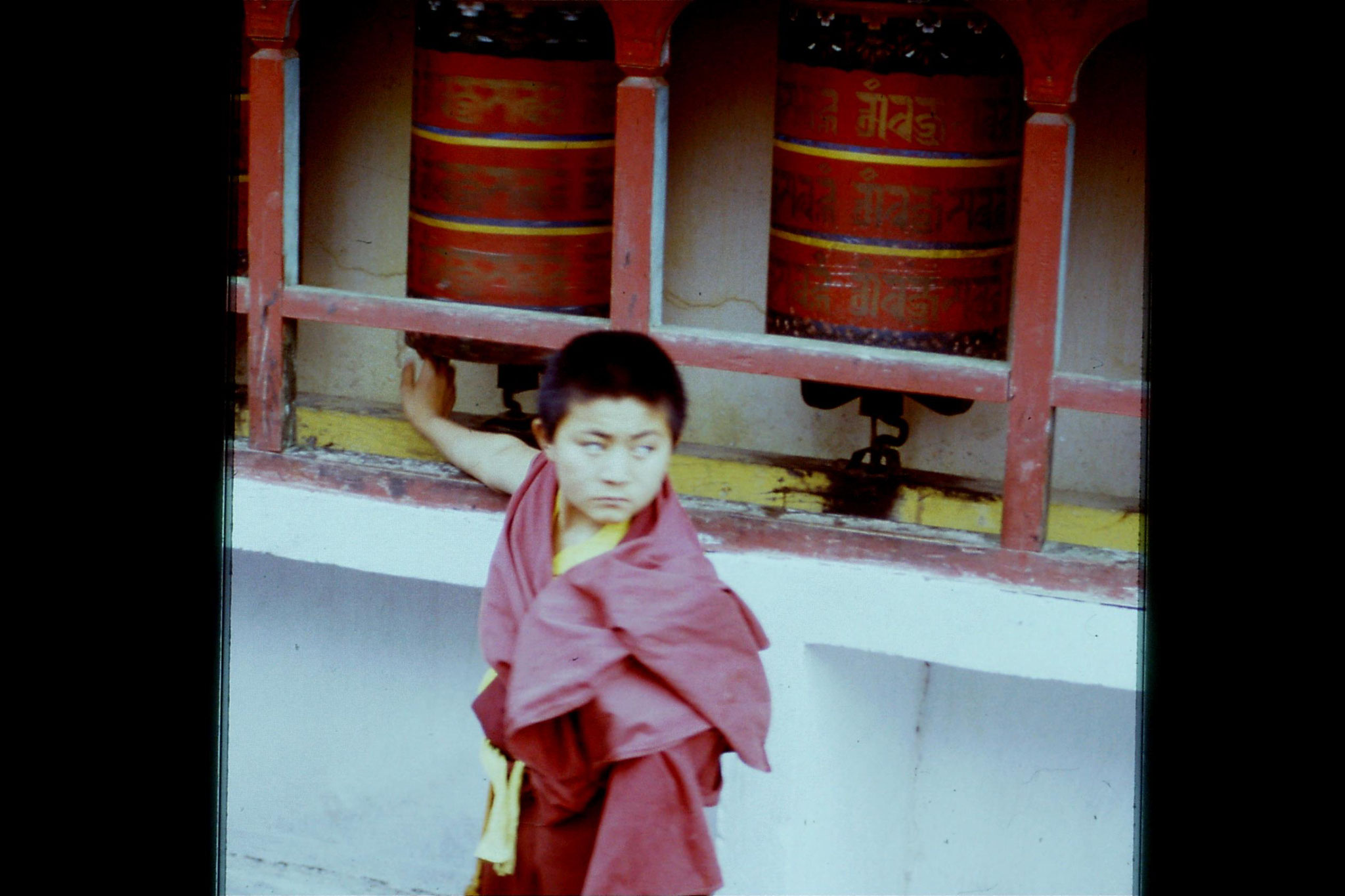 115/13: 23/4/1990 Rumtek - prayer wheel and boy monk