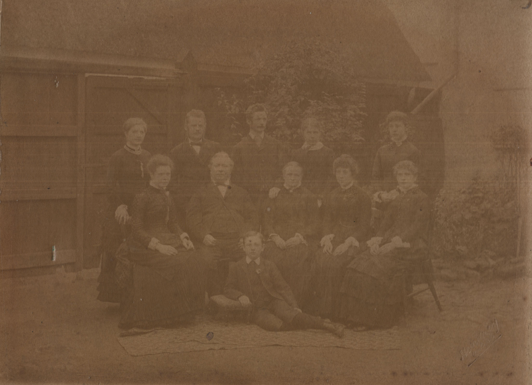 The Hodson Family, Elsworth, Brook Street. From left right, back row, Alberta, ?,?,?, Flora; middle row, ?, William, Jane, Clara Jane, ?; Martin in front.