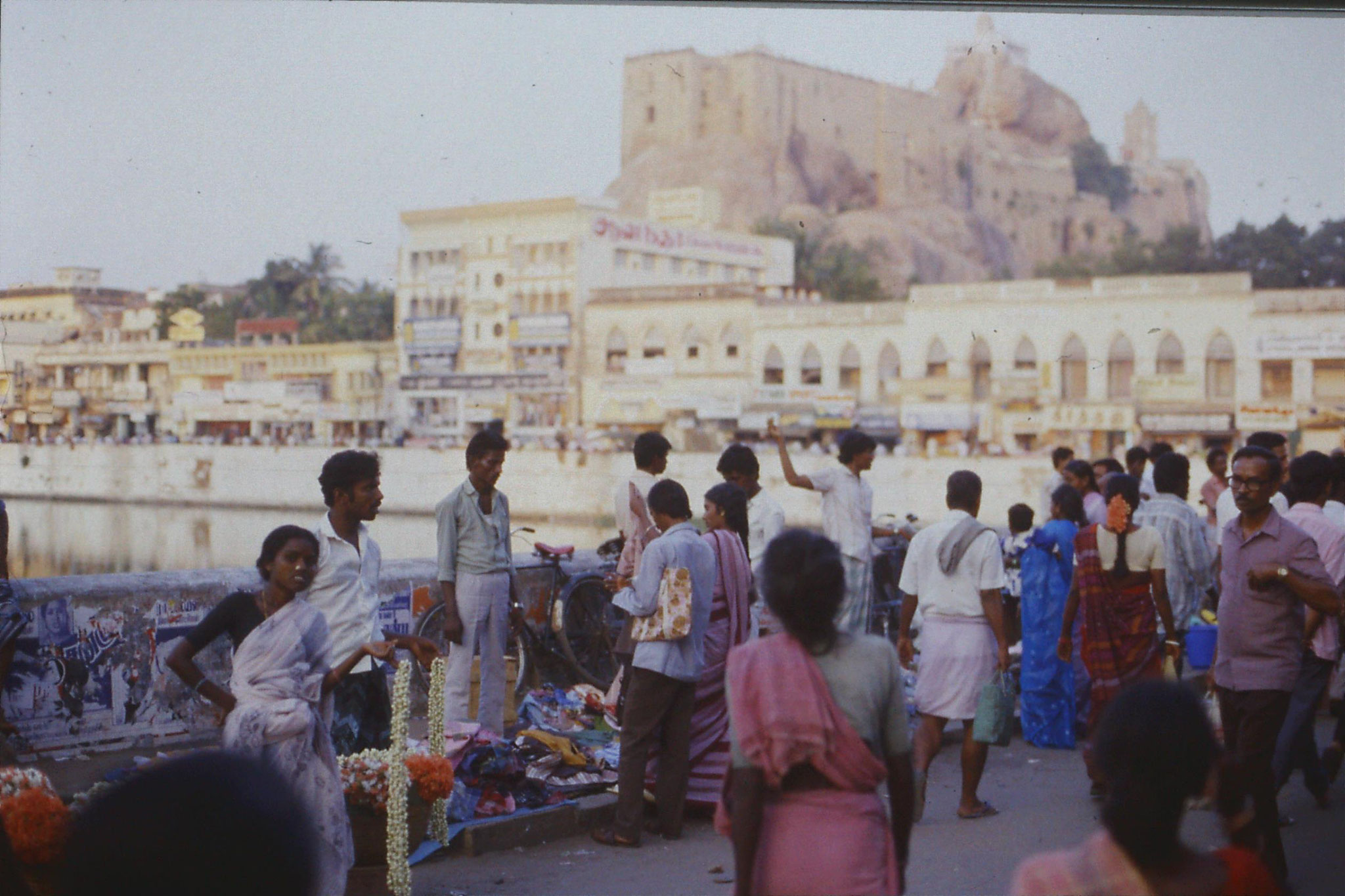 104/19: 13/2/1990 Trichy, flower sellers by tank, rock fort behind