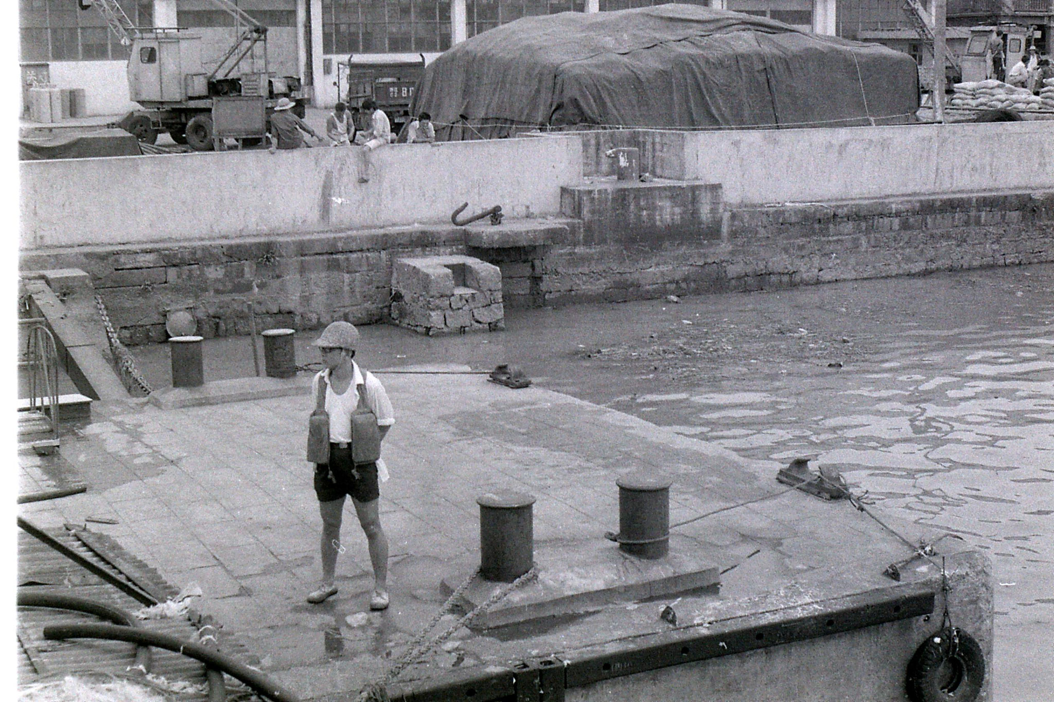 23/7/1989: 26: man untying our ship at Ningbo with bamboo helmet