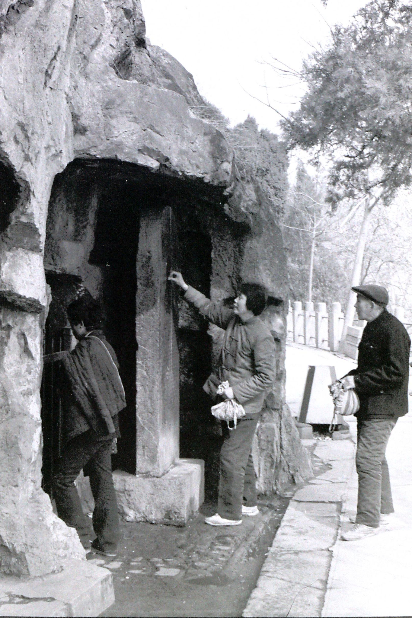 28/2/1989: 6: Luoyang Longmen Caves, putting coin in stele