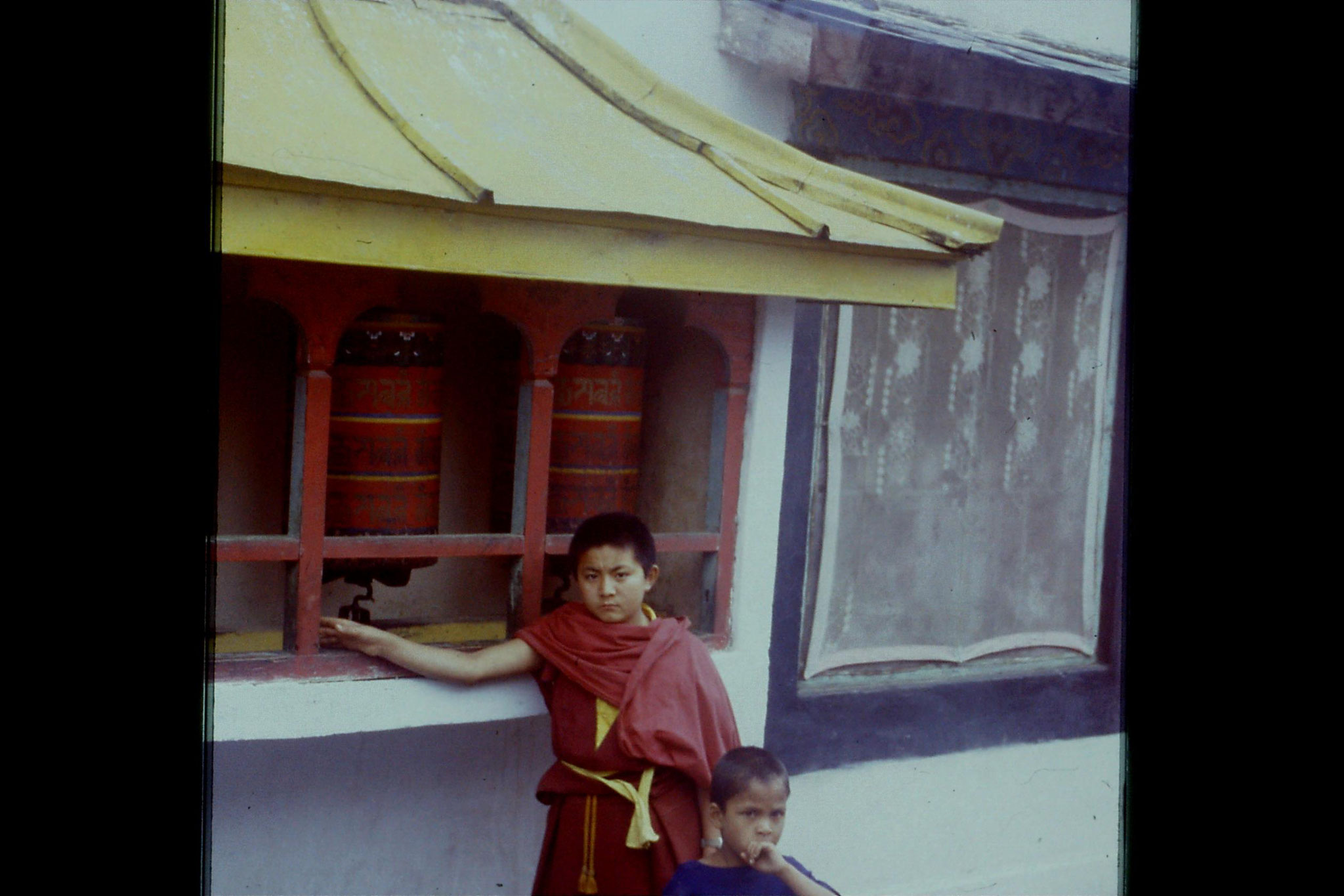 115/14: 23/4/1990 Rumtek - prayer wheel and boy monk