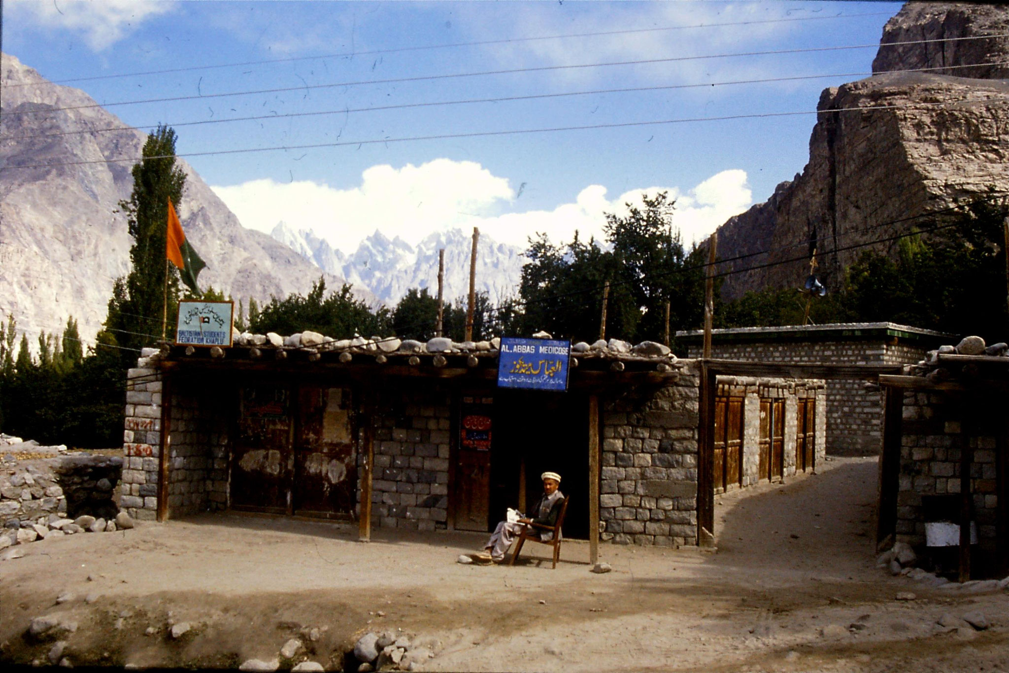 15/10/1989: 29: Khaplu, chemist at shop with PPP flag, mosque