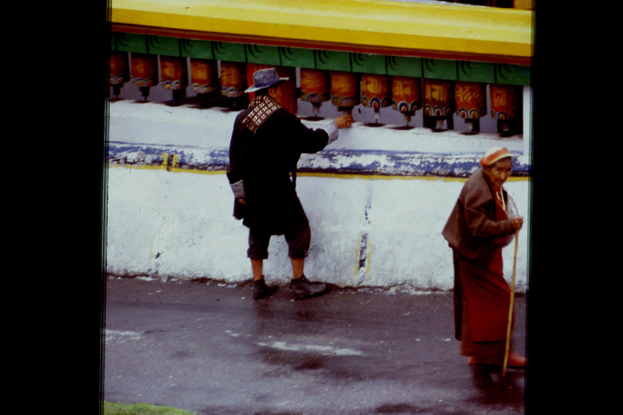 115/12: 23/4/1990 Rumtek - man turning prayer wheel