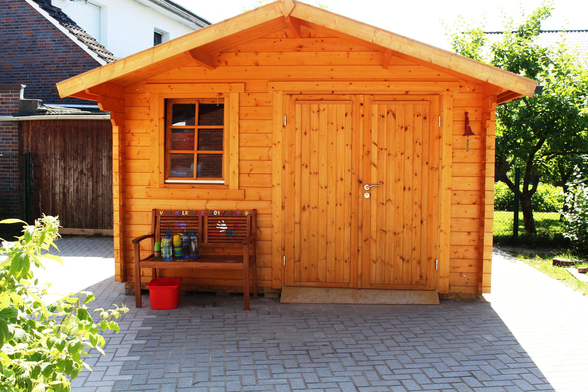 Holzhaus mit Fahrzeugen und Sandspielzeug