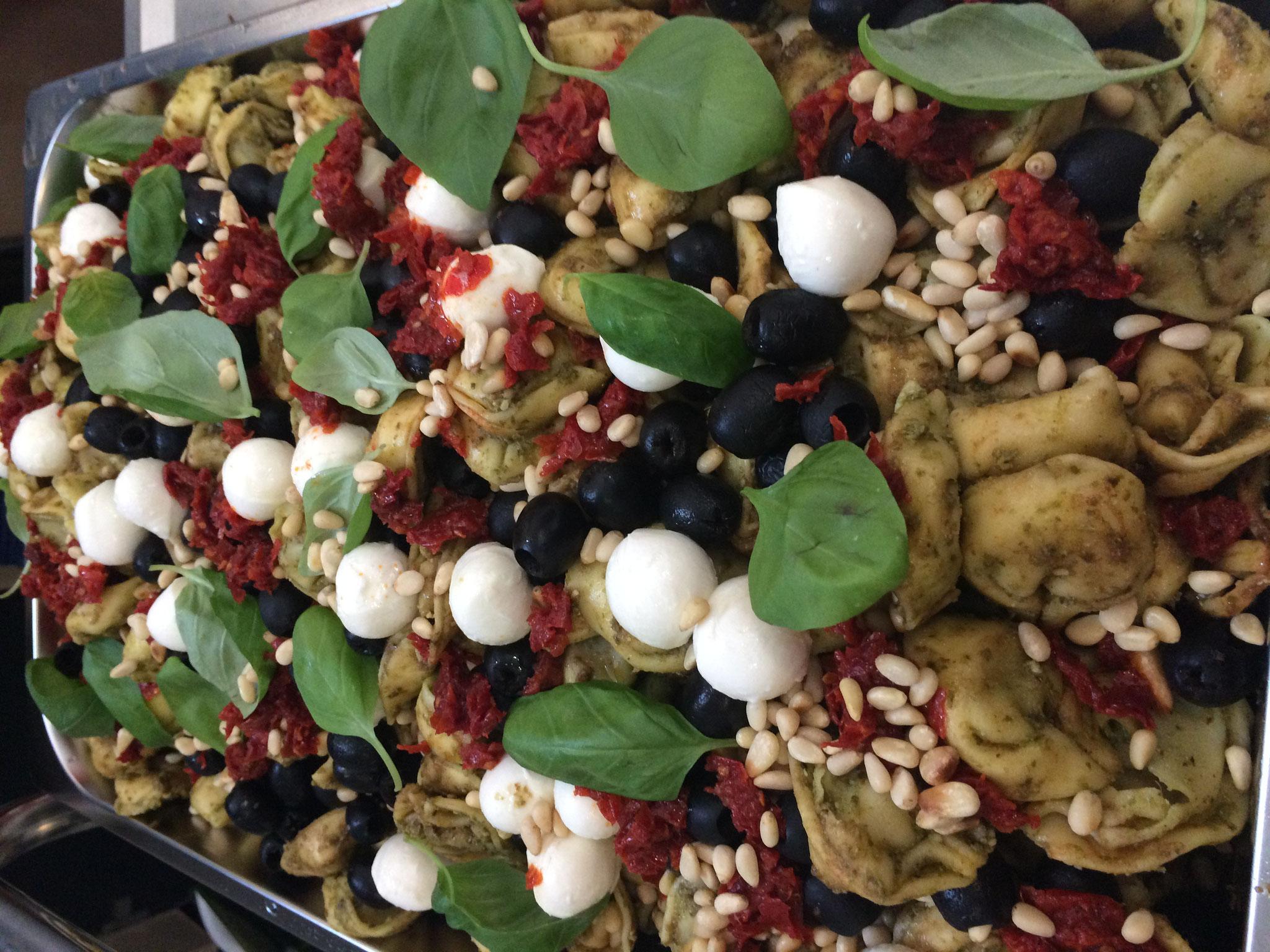 Tortellinisalat mit Pesto, Mozzarellakugeln, Oliven Tomaten, Pinienkerne und Basilikum