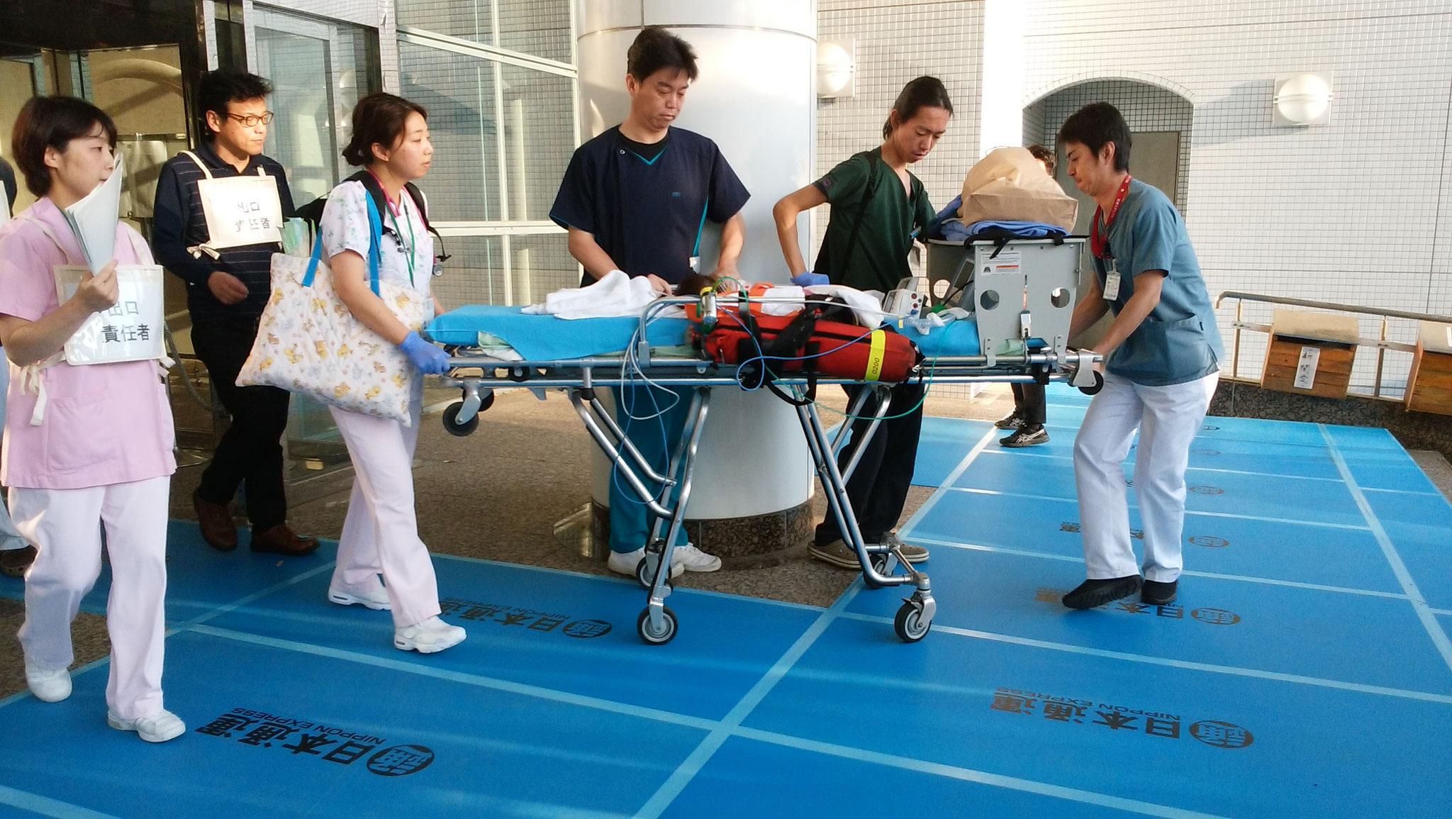 週産期医療センター玄関から小児患者が救急車へ移動中