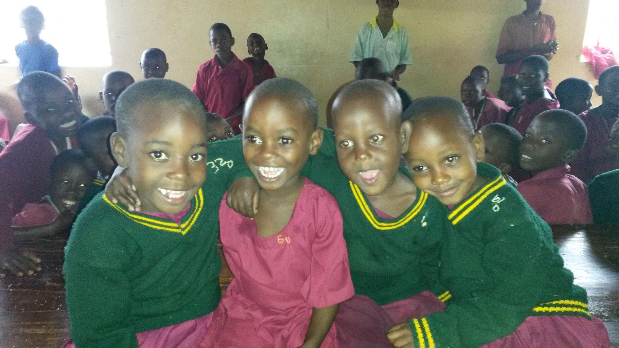 Justine, Patricia, Amina und Praise-Natascha im Speisesaal. Die Kinder im Hintergrund entfernen die Maiskörner von den Maiskolben.