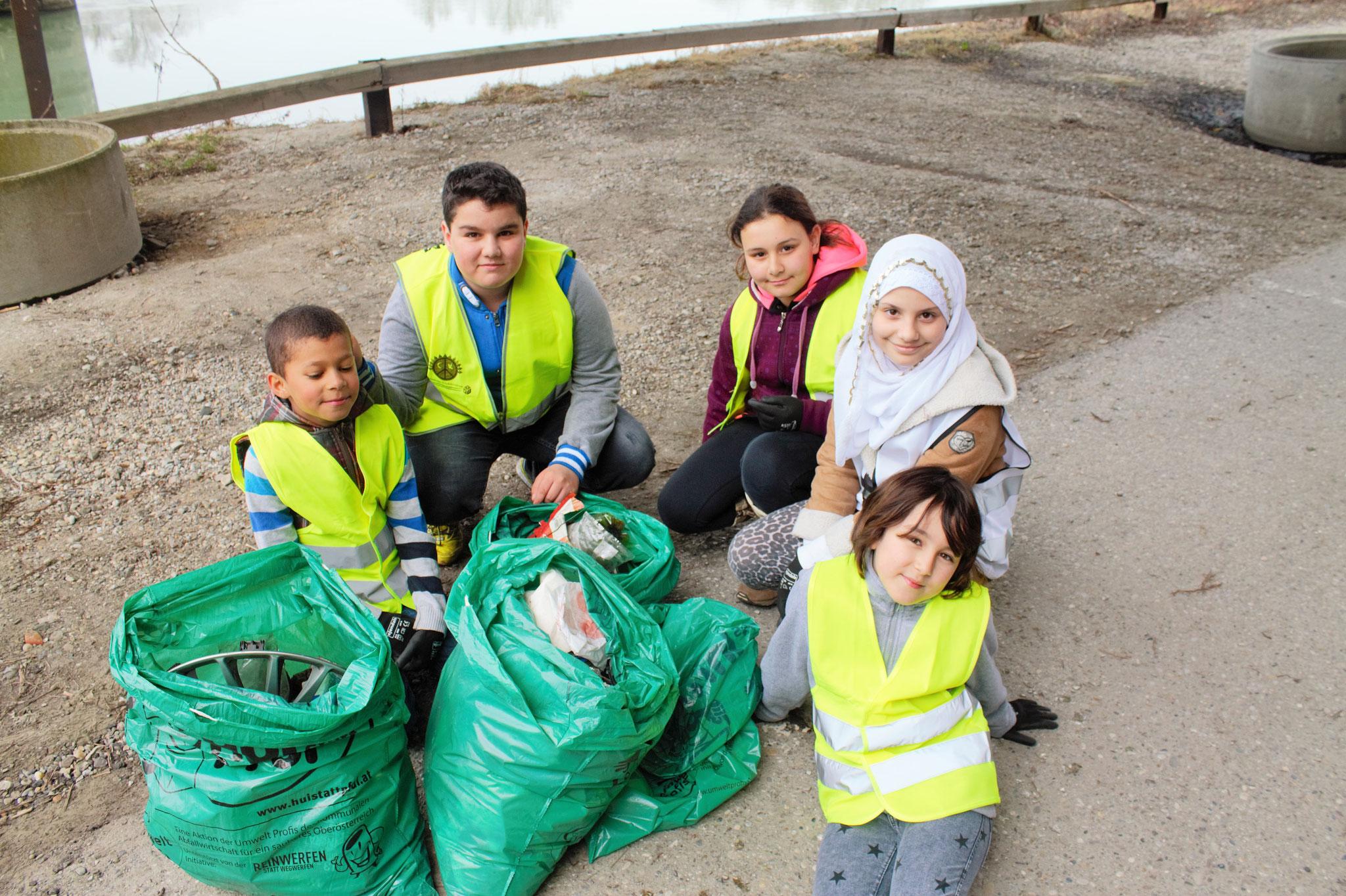 Umweltprofis zeigen den gesammelten Müll
