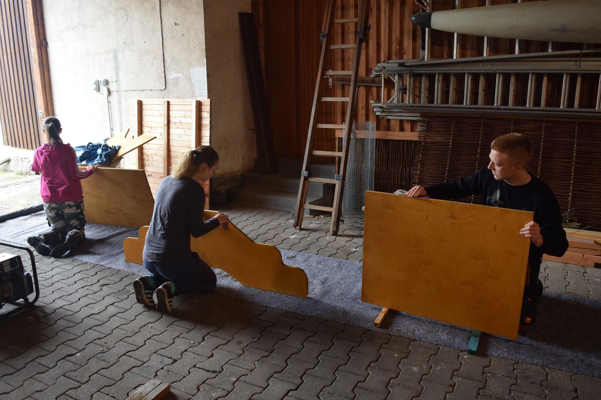 Schleifen der bereits einmal lasierten Schilder und Flügel im Bauhof, bevor eine zweite Schicht Lasur aufgetragen wird - sie sollen ja lange halten :)