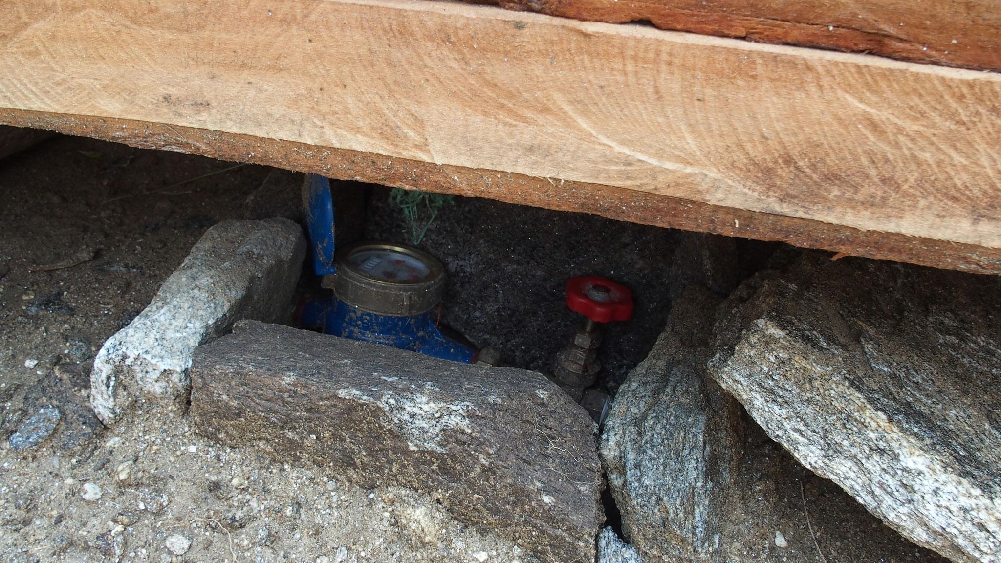 Les vannes et compteurs sont installés et protégés près de chaque maison.