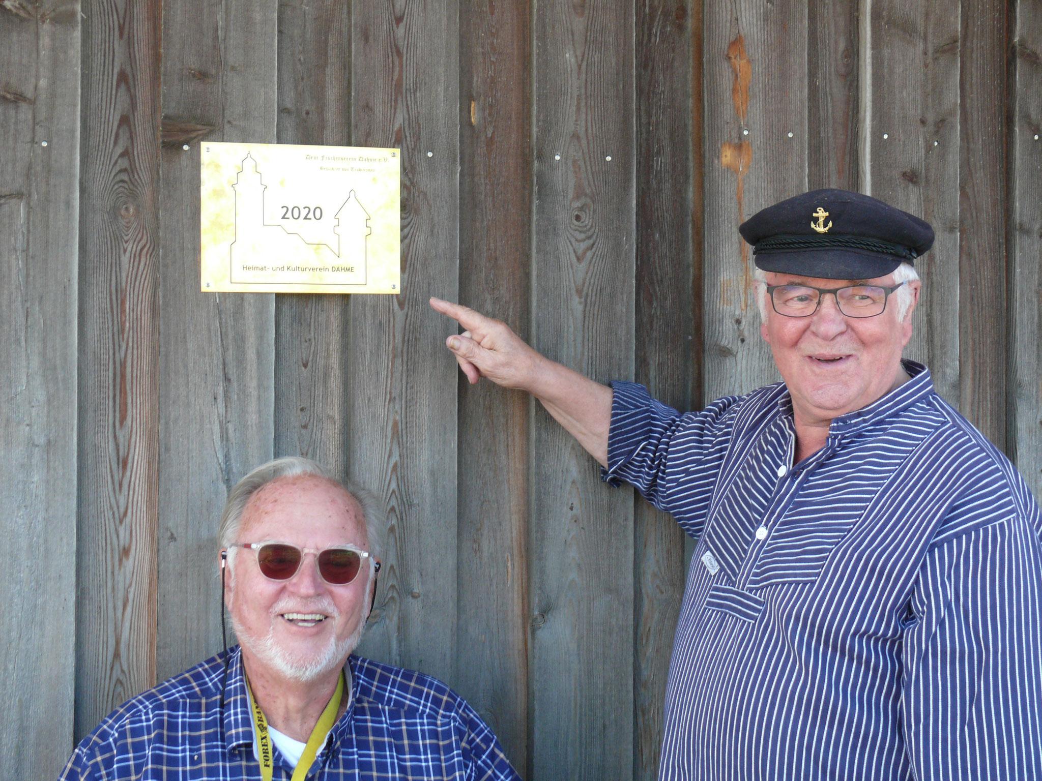 Die Vorsitzenden vom Heimat- und Kulturverein, Jürgen Möller (links), und Fischerverein, Rudi Höppner (rechts), vor der Auszeichnungsplakette.