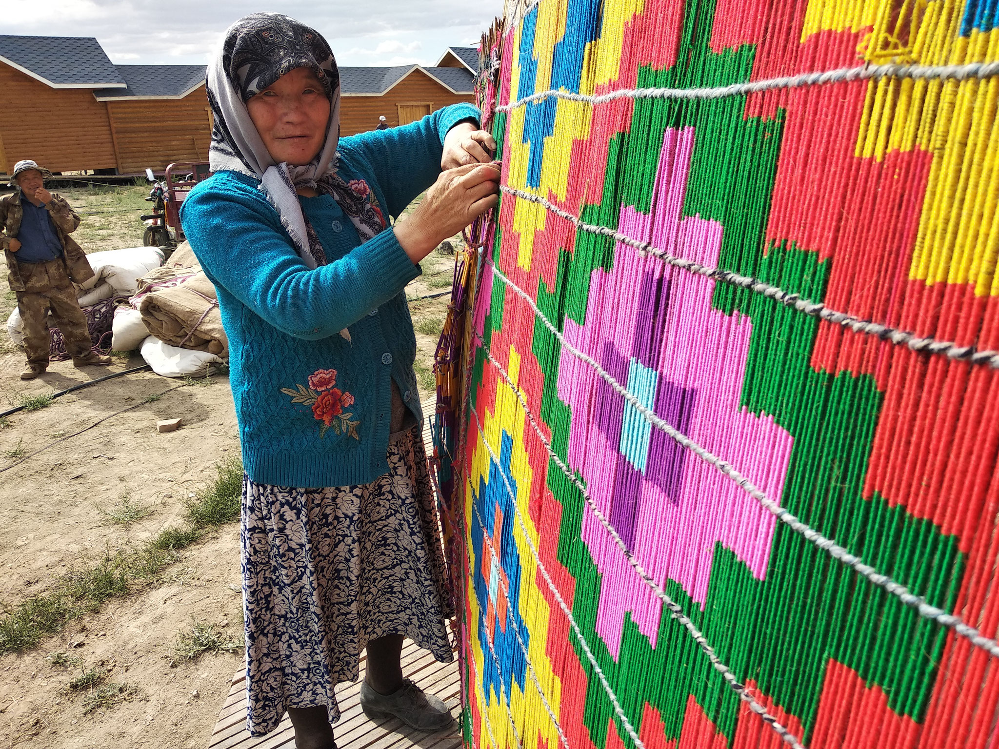 A Kazakh woman securing the straw-mat siding of the yurt.